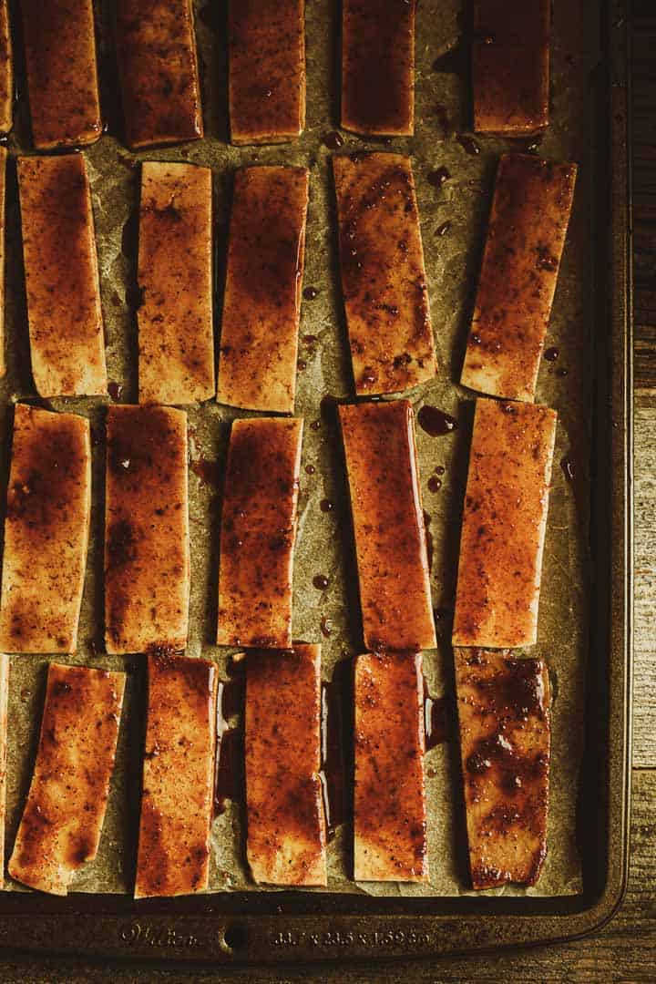 Marinated tofu strips on baking sheet.