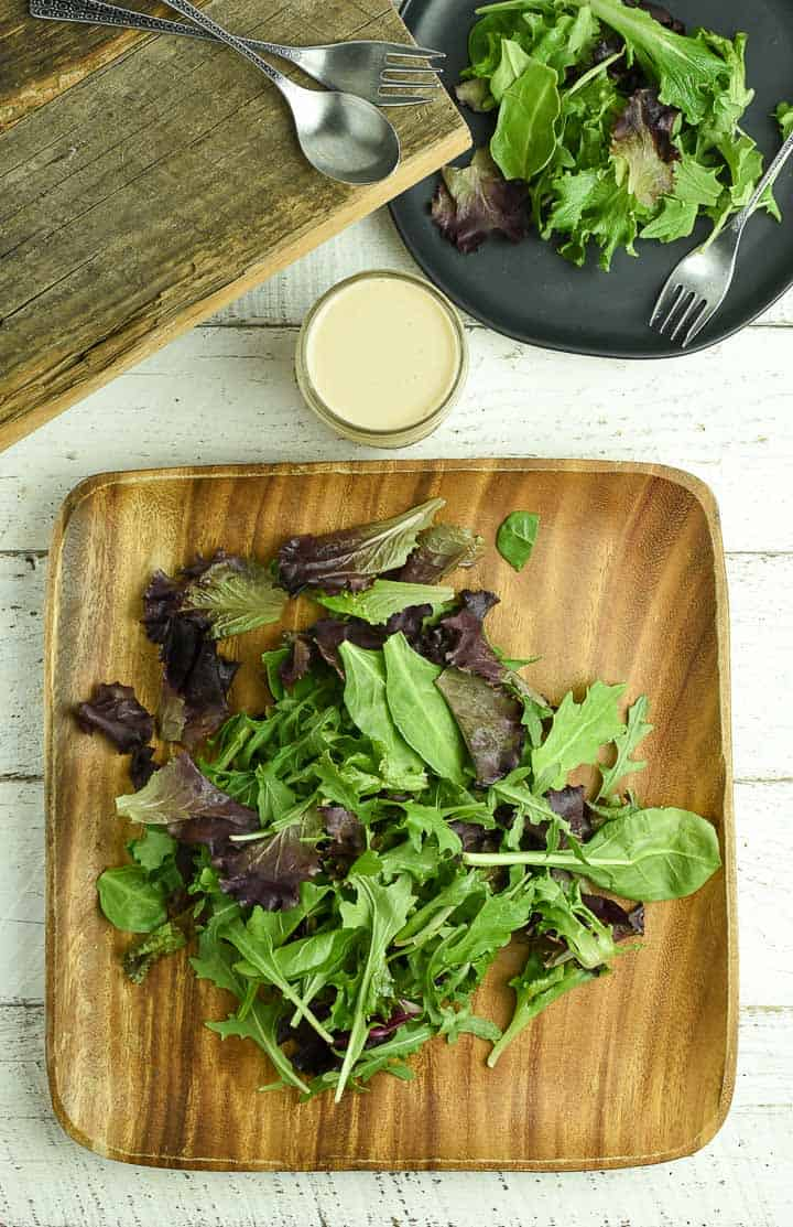 Salad on wooden plate with tahini dressing in bottle