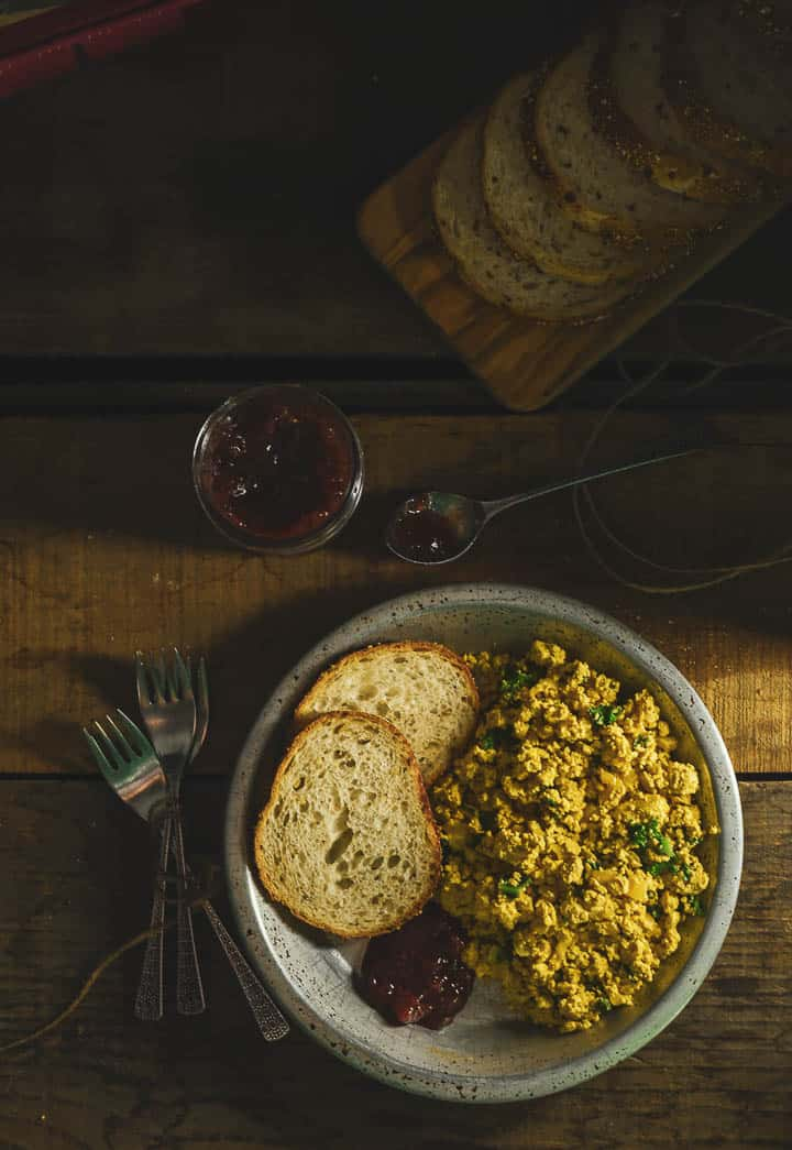 Vegan tofu scramble in tin plate with 2 slices of toast on table with forks and loaf of bread.