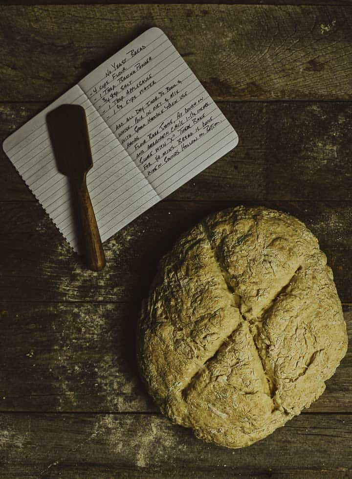 No yeast bread on table with notebook and knife.