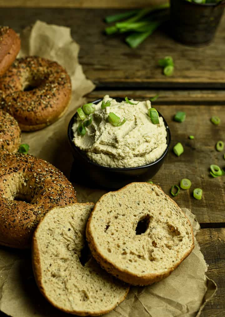 Vegan cream cheese in black bowl with chopped green onions and surrounded by bagels.