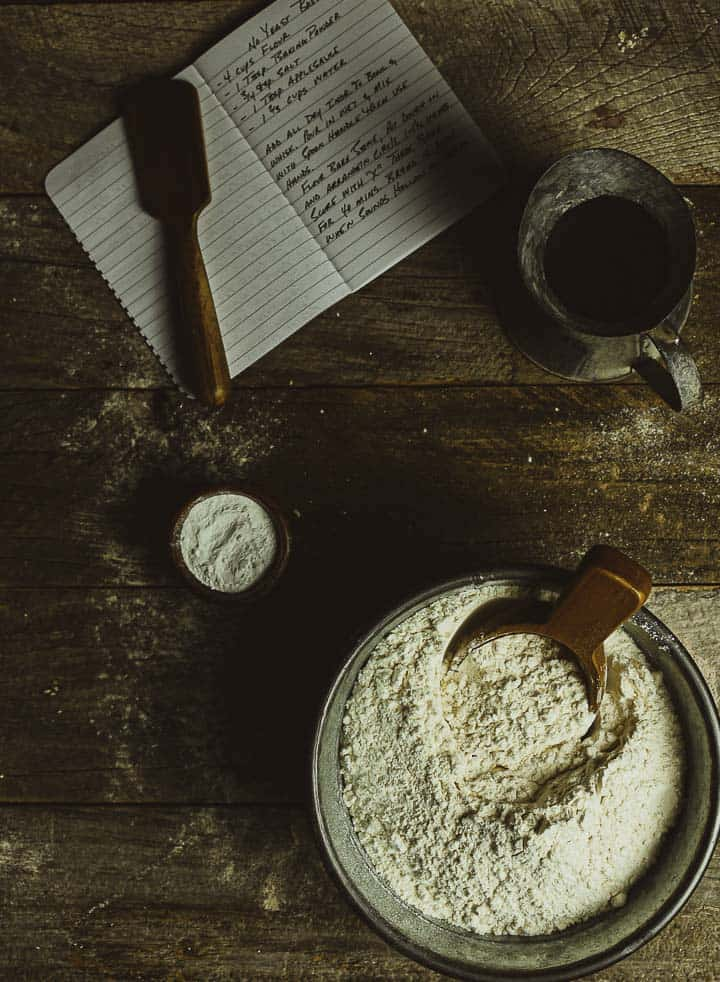 bowl of flour and notebook with recipe.