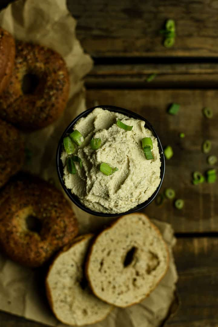 Black bowl of vegan cream cheese topped with green onion.