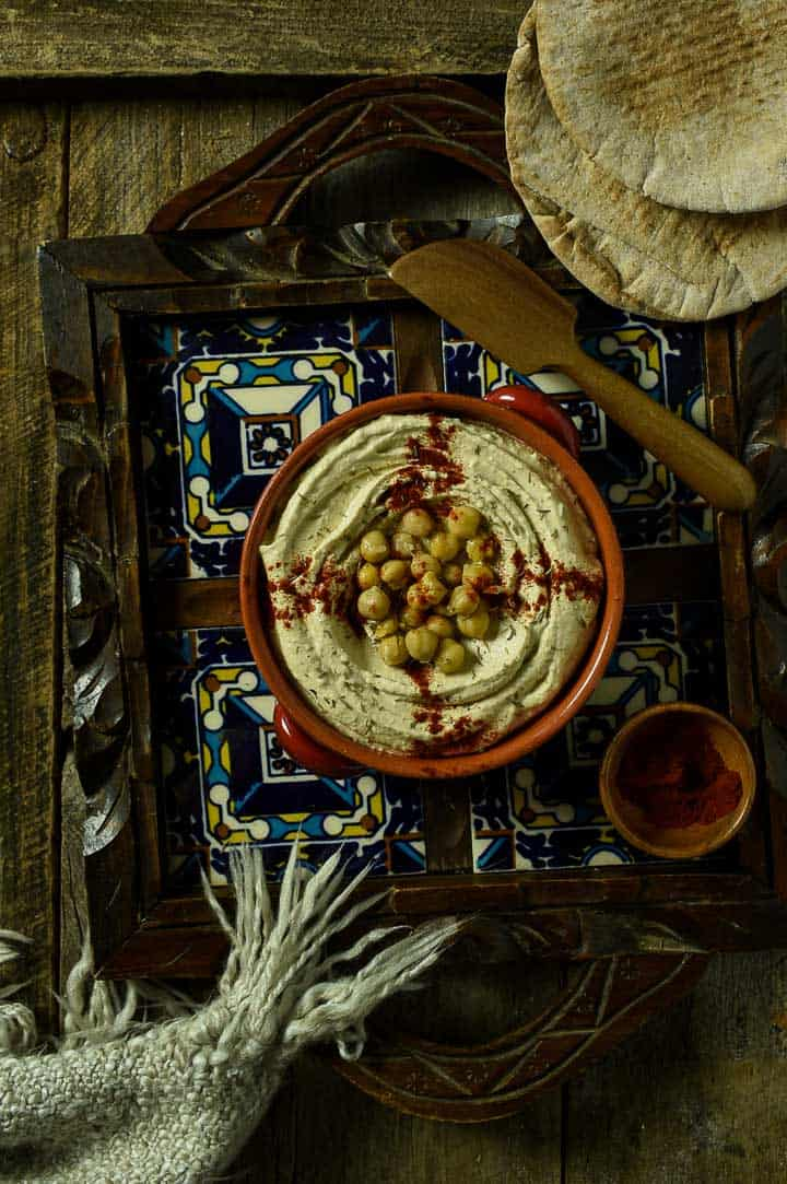 hummus with paprika in a bowl on a tray.