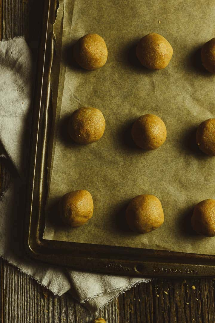 cookie dough balls on baking sheet with parchment paper.