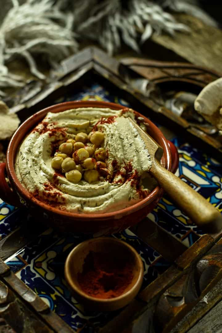 Bowl of hummus with spoon.