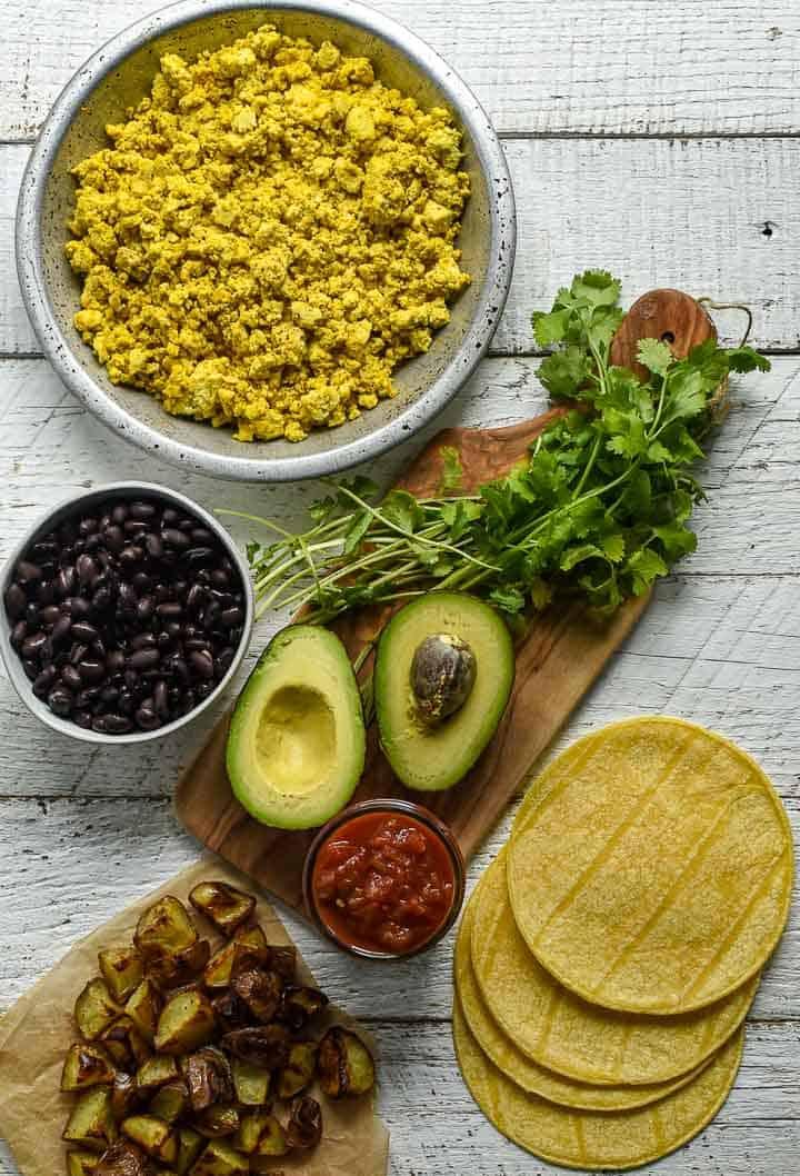 Tofu scramble, black beans, corn tortillas, avocado, and salsa on table.