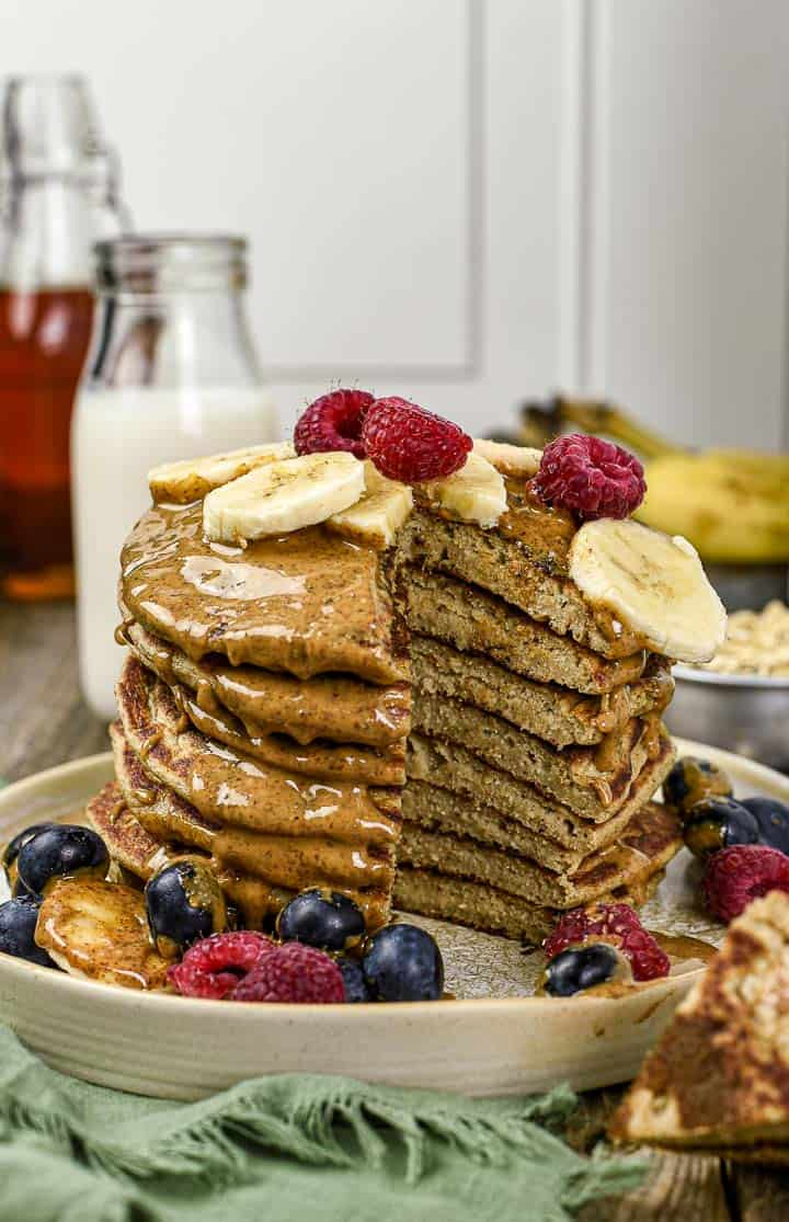 Banana Oat pancakes stacked, cut, and covered in almond butter, bananas, blueberries, and raspberries.