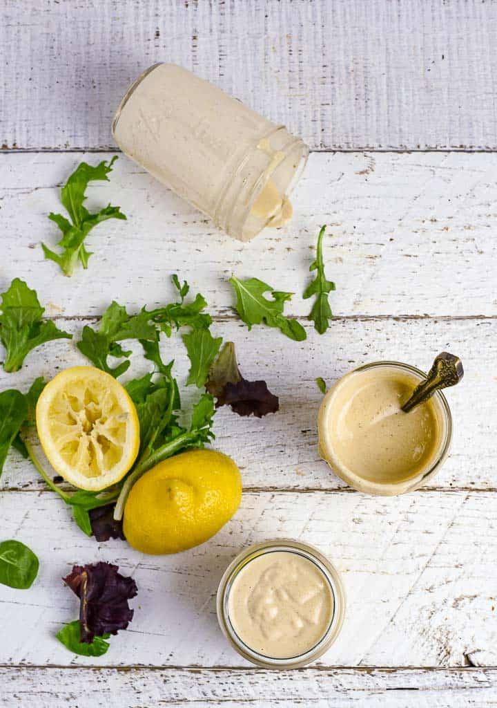 Lemon tahini dressing on white table with greens and lemons.