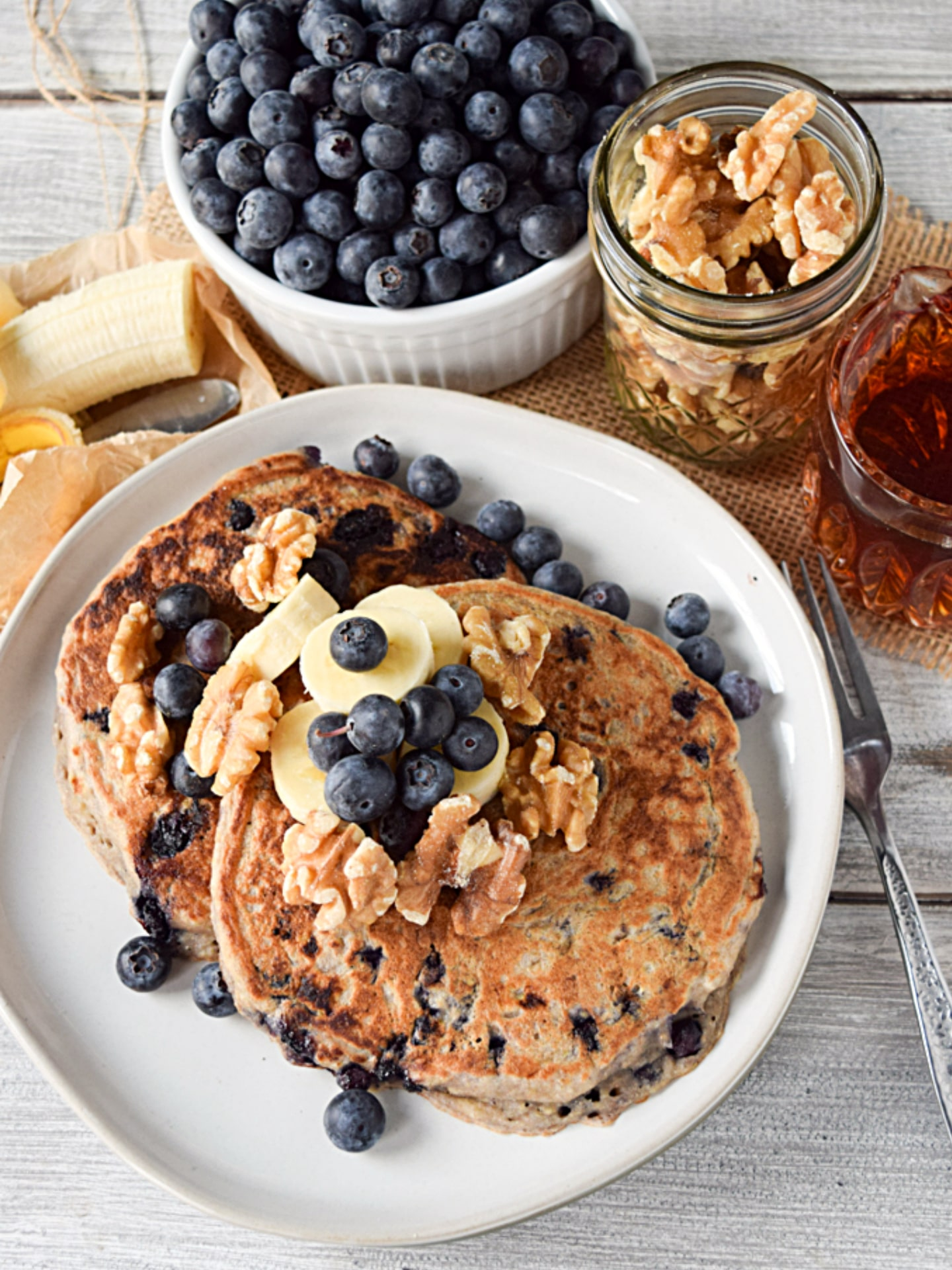 vegan blueberry pancakes on plate with bananas and walnuts.