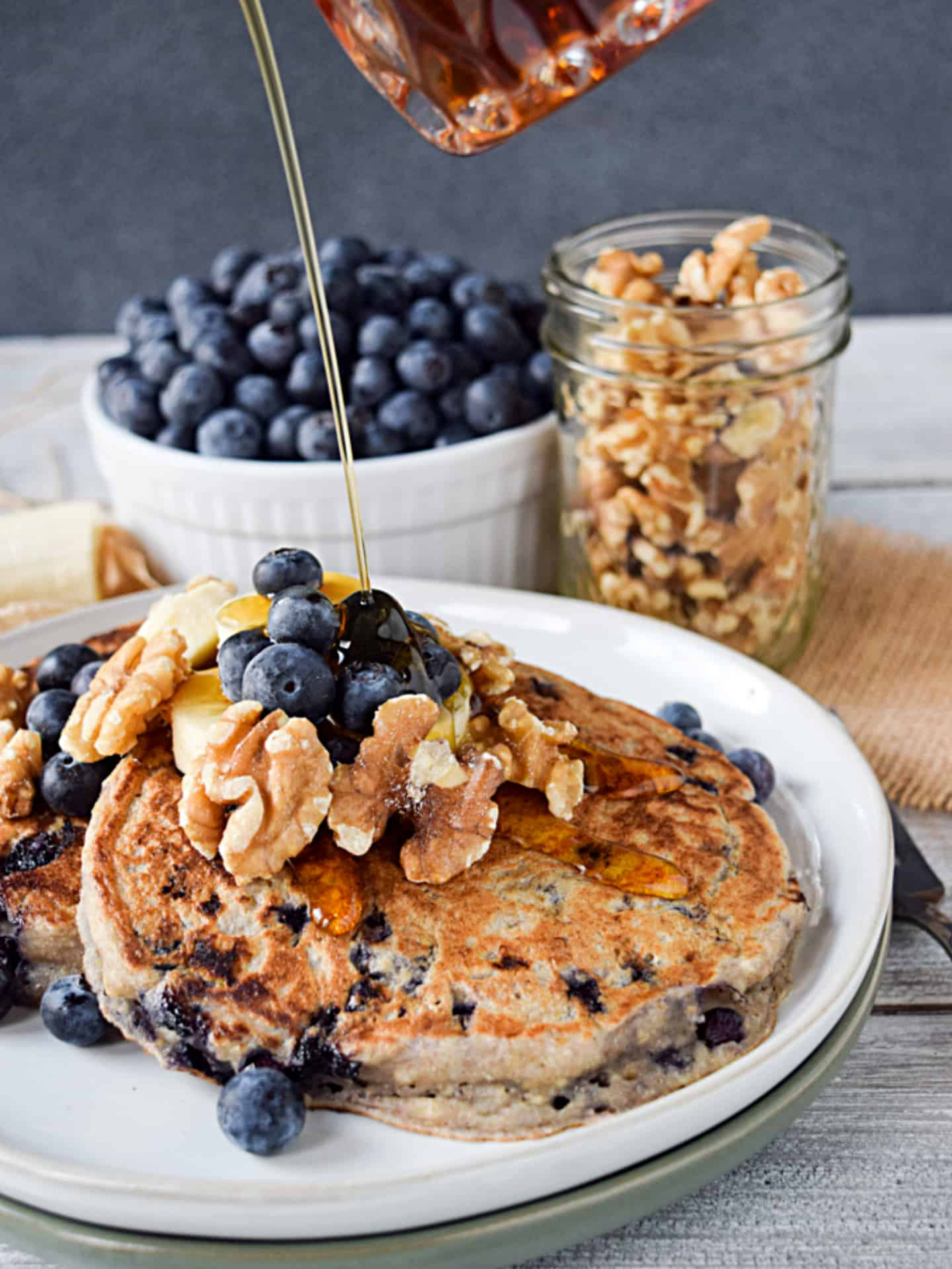Maple syrup over blueberry pancakes with bananas and walnuts.