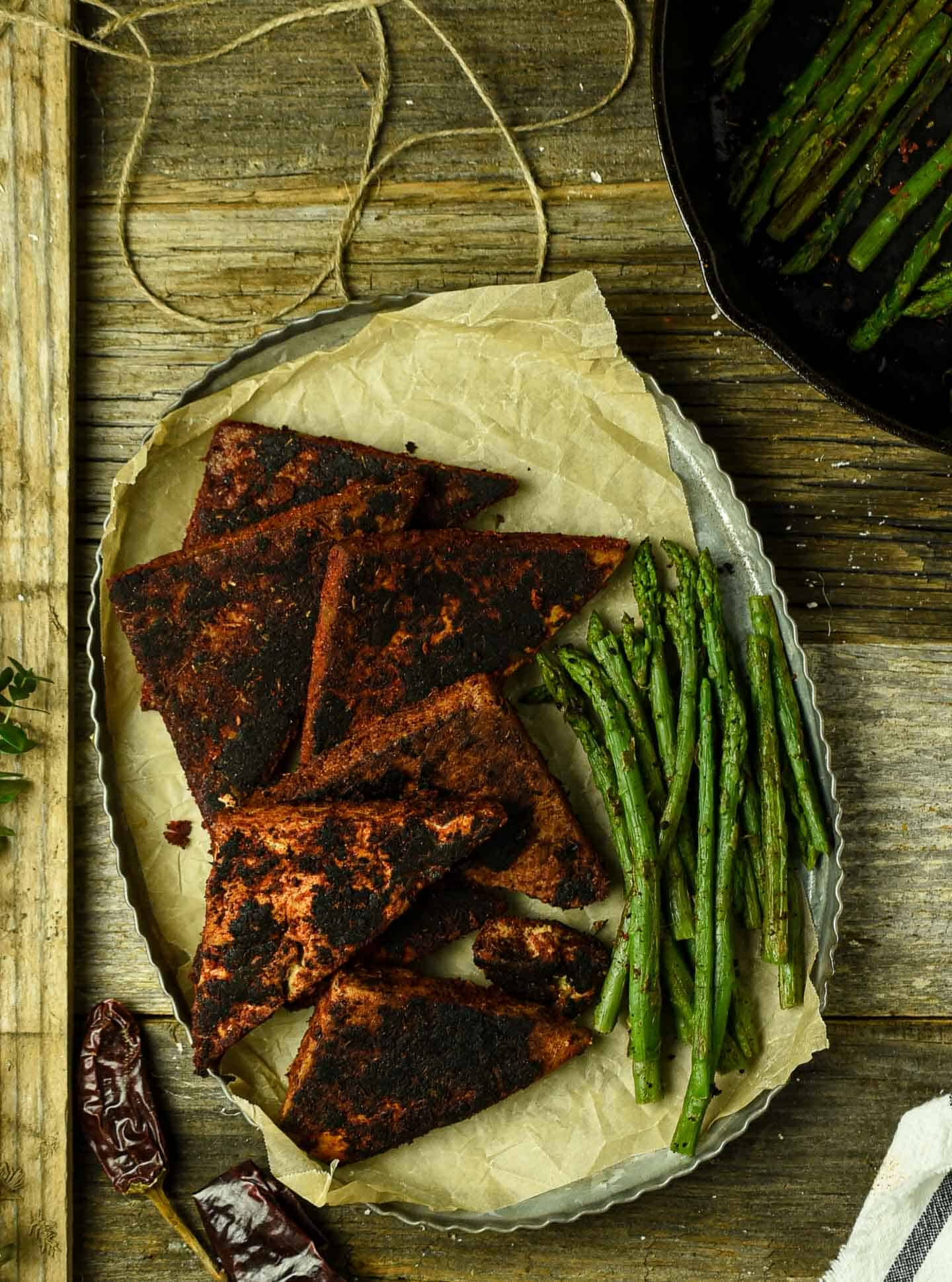 Blackened tofu steaks on tray with asparagus.