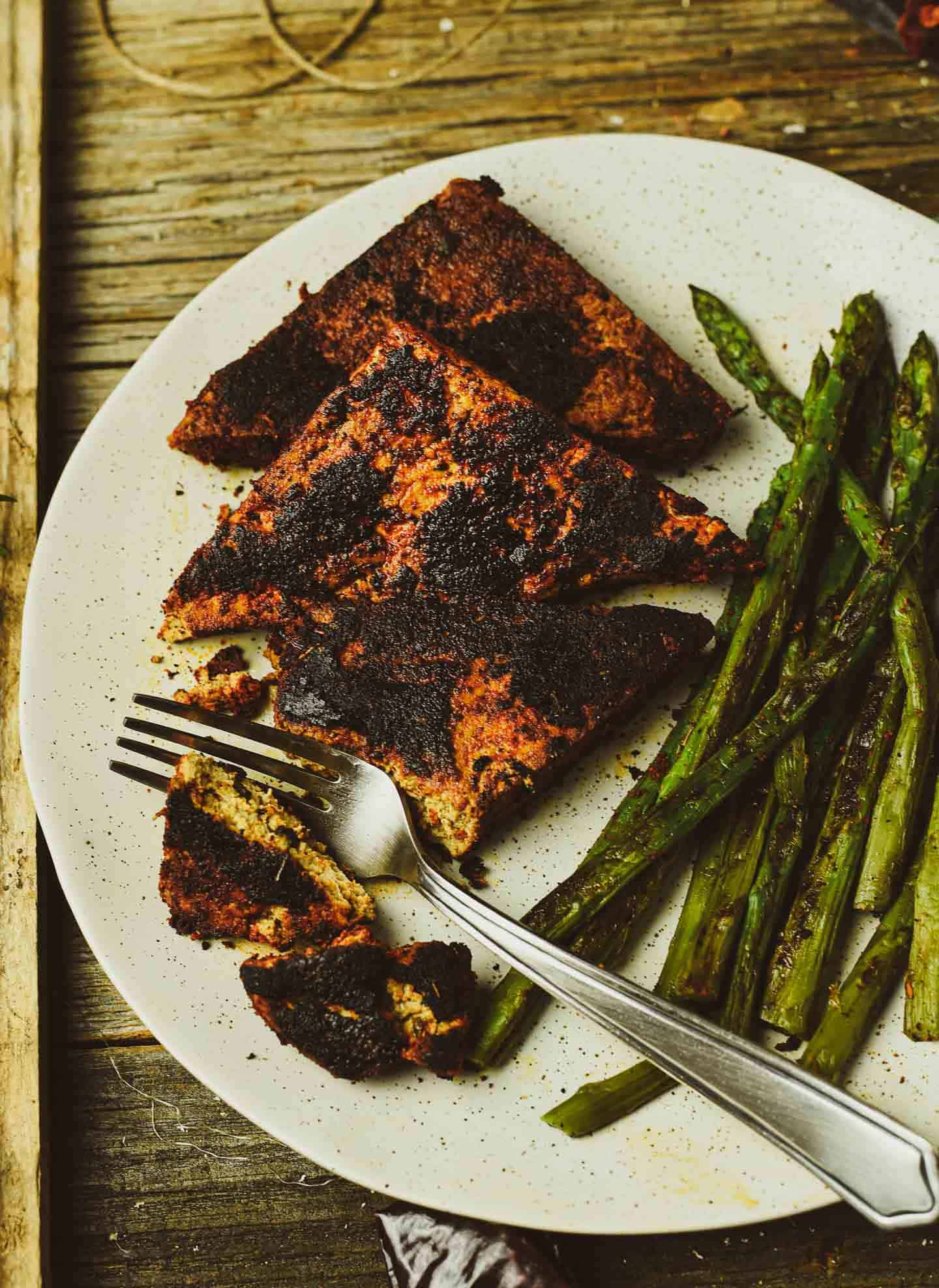 Tofu steaks on plate with asparagus.