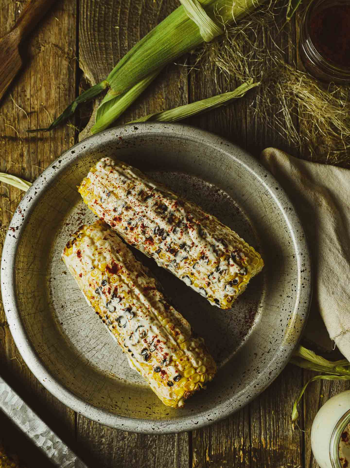 Corn on the cob with vegan mayo and smoked paprika spread.