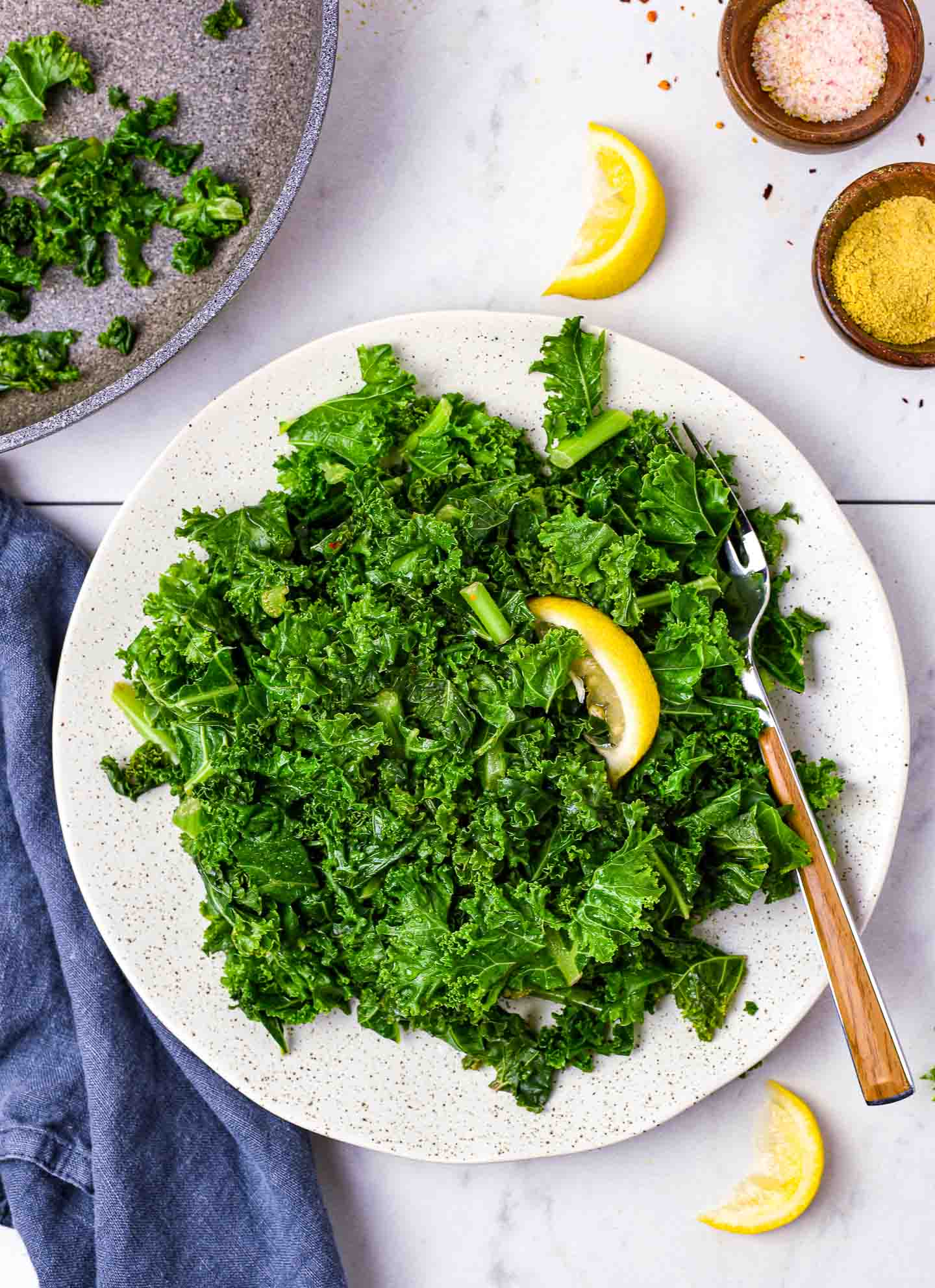 Sauteed kale on plate with lemon and fork.