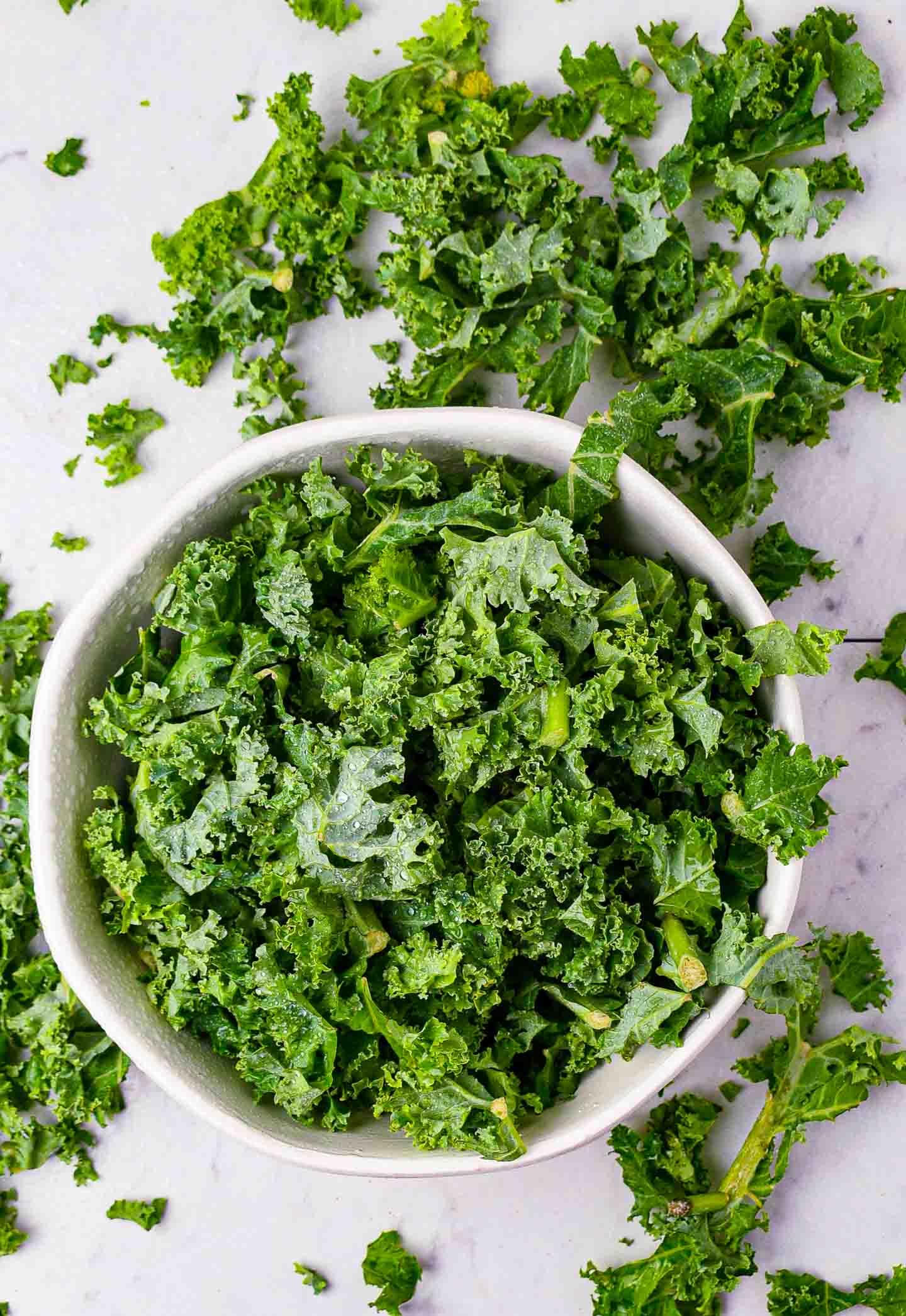 Raw chopped kale in white bowl.