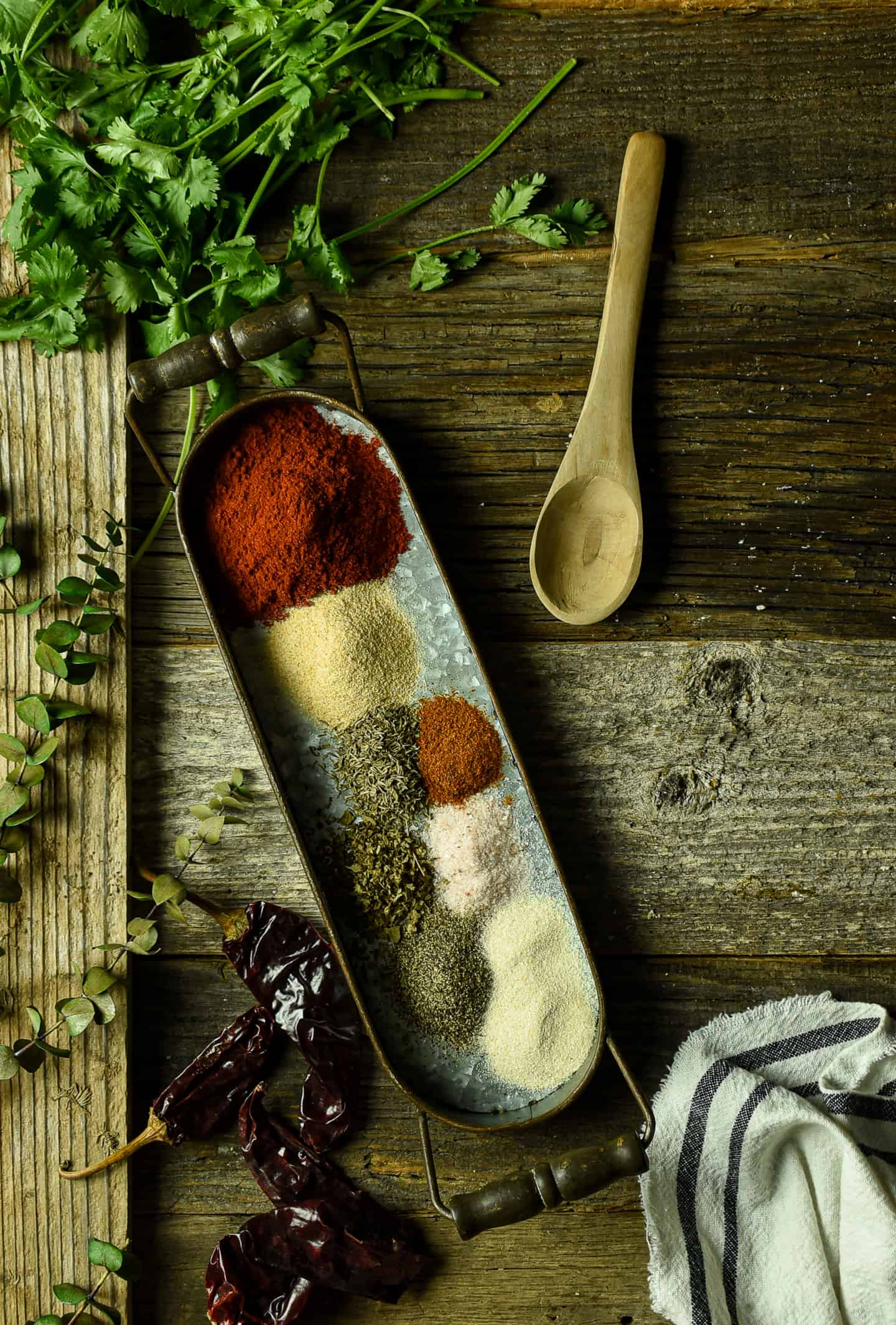Spices on tray with wooden spoon.