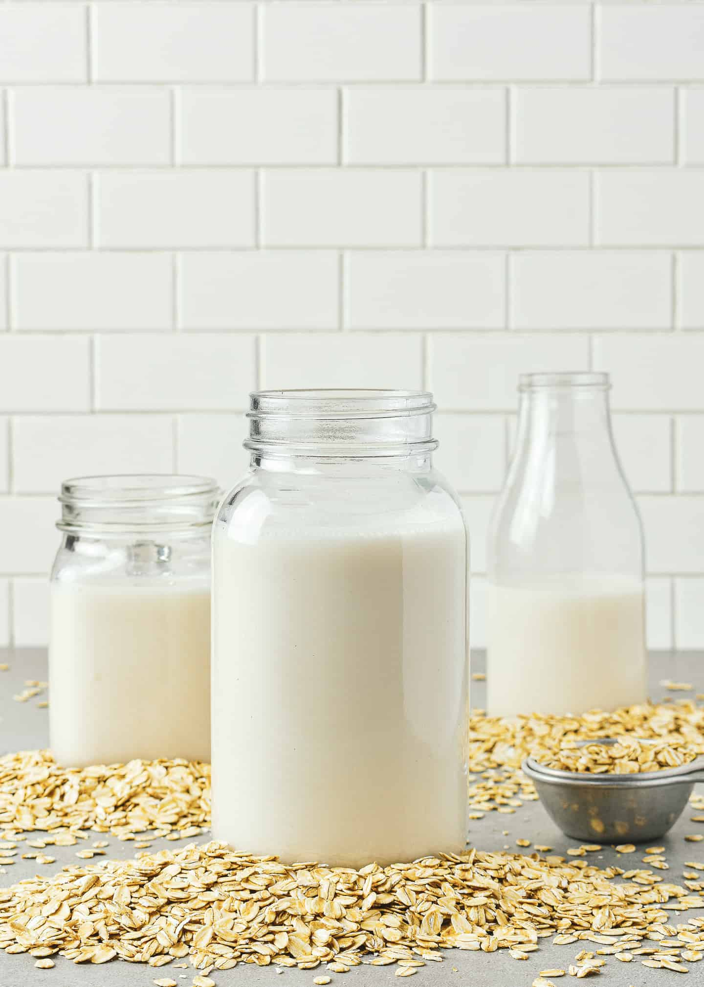 3 jars of oat milk with oats scattered on table.