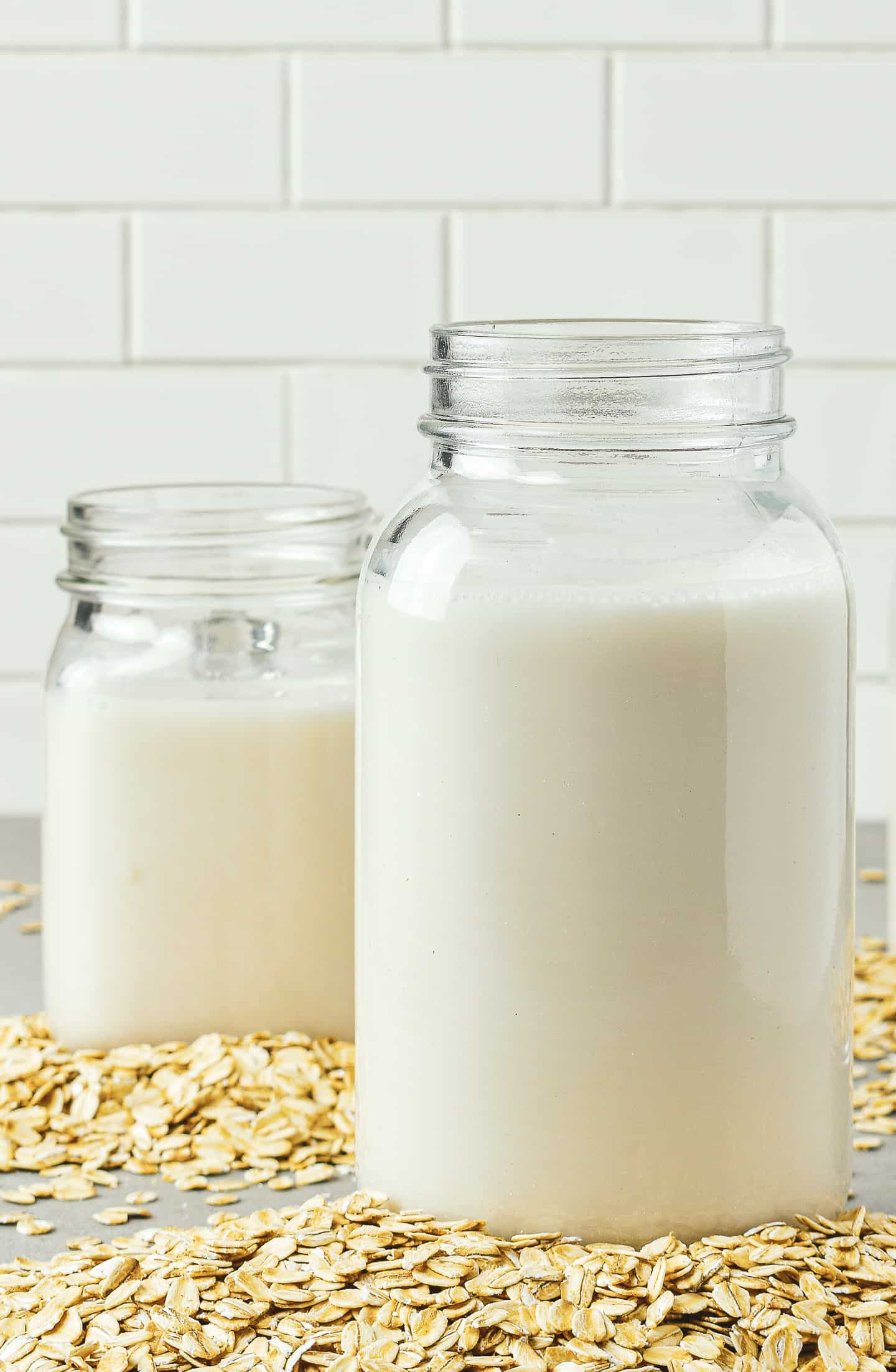 Two jars of oat milk with oats on table.