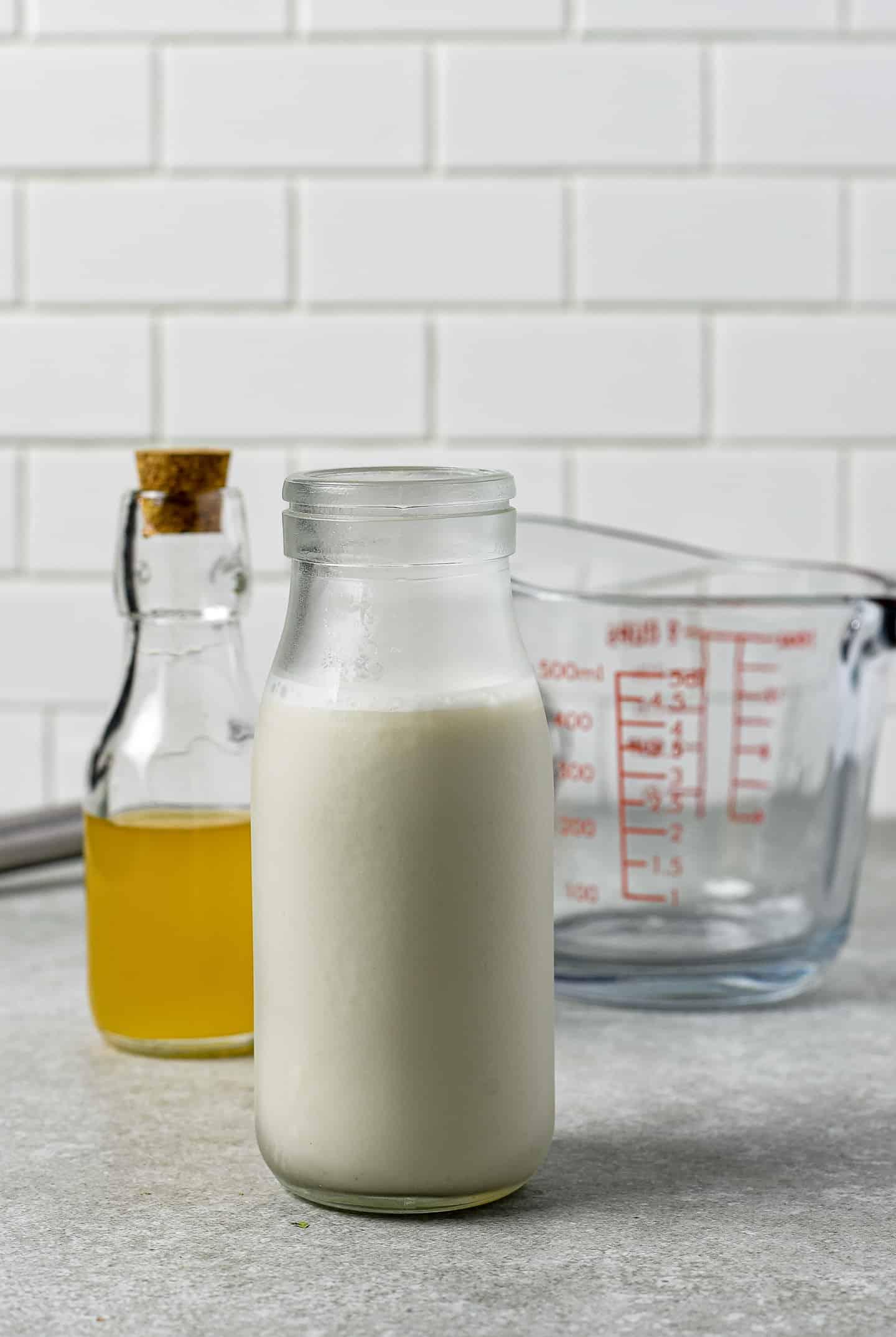 Almond milk, apple cider vinegar, and pyrex measuring cup.