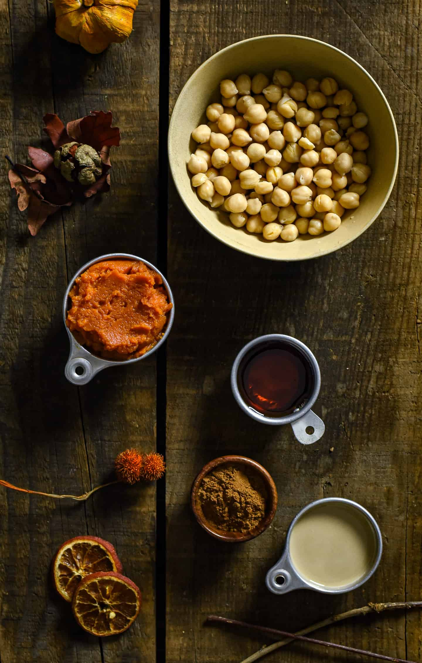 chickpeas, canned pumpkin, maple syrup, cinnamon, and tahini in measuring cups.