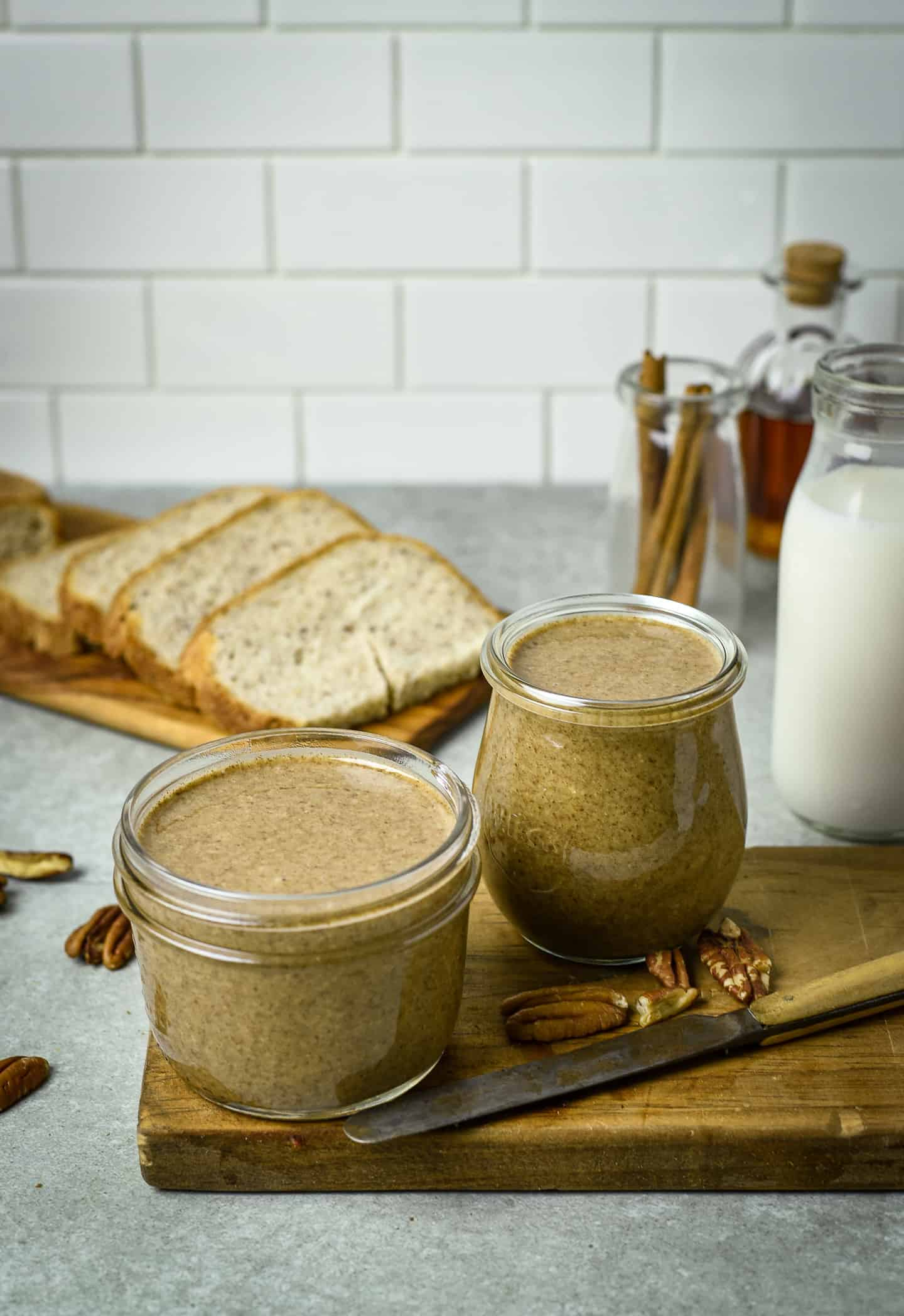 Pecan nut butter in two jars on table with loaf of bread.