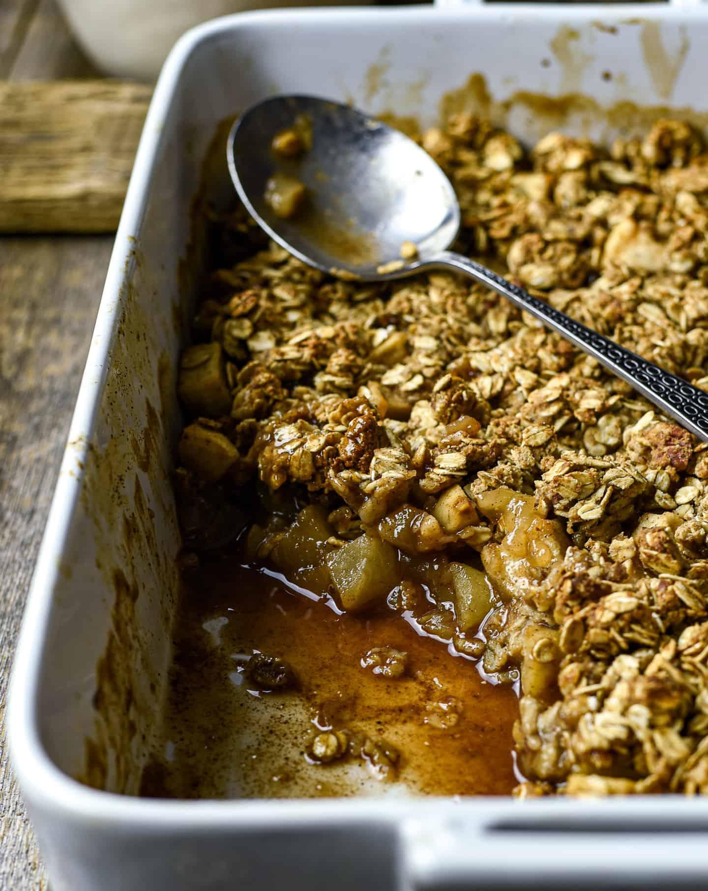 vegan apple crisp in baking dish with spoon.