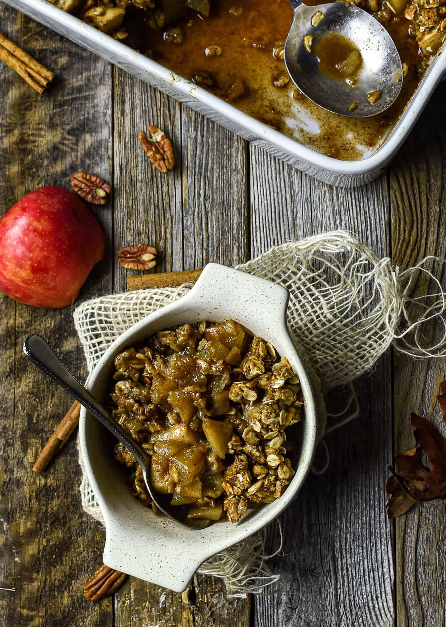 vegan apple crisp in bowl with spoon.