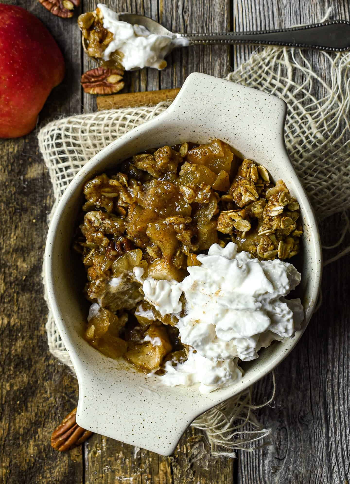 vegan apple crisp in bowl with vegan whipped cream.