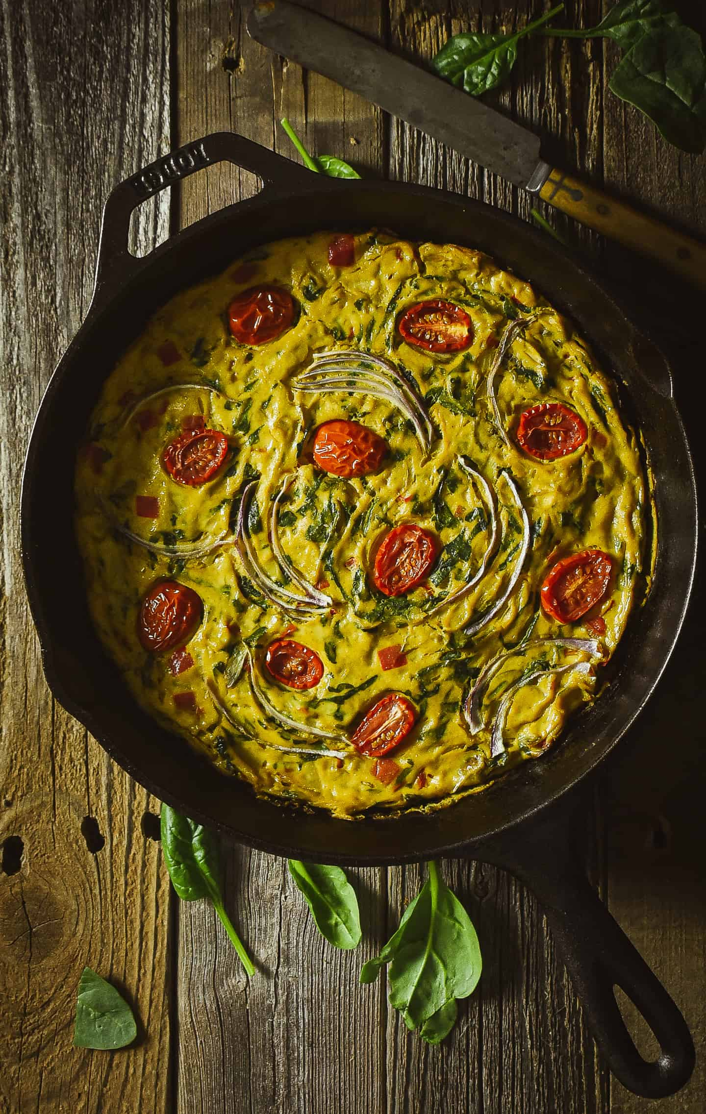 Vegan frittata topped with onions and grape tomatoes in cast iron skillet.