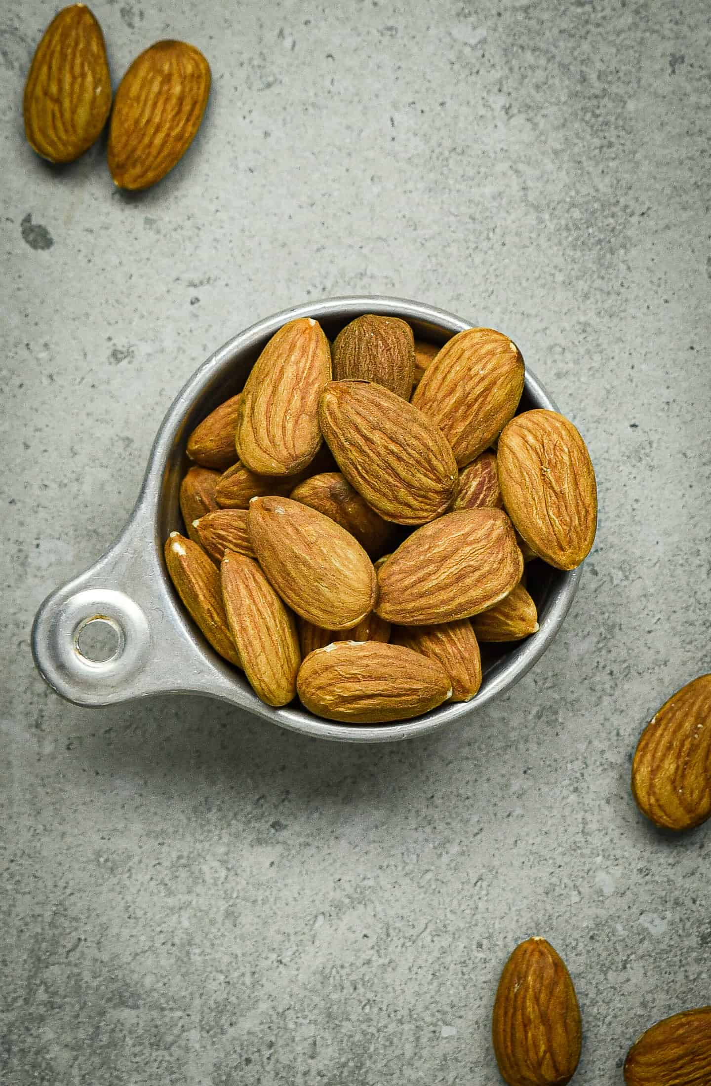 Measuring cup filled with almonds.