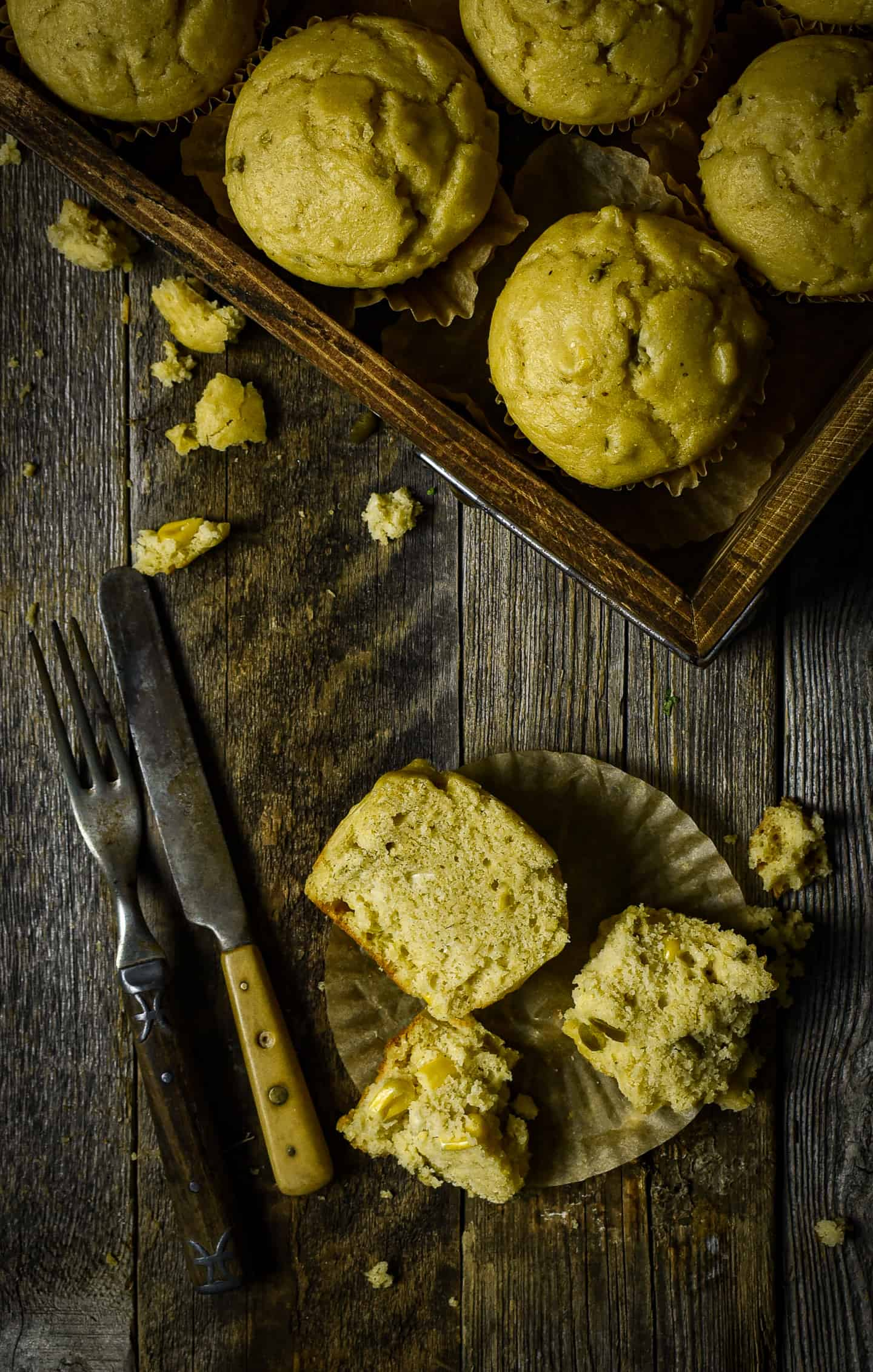 Corn bread muffin cut in half with knife and fork.