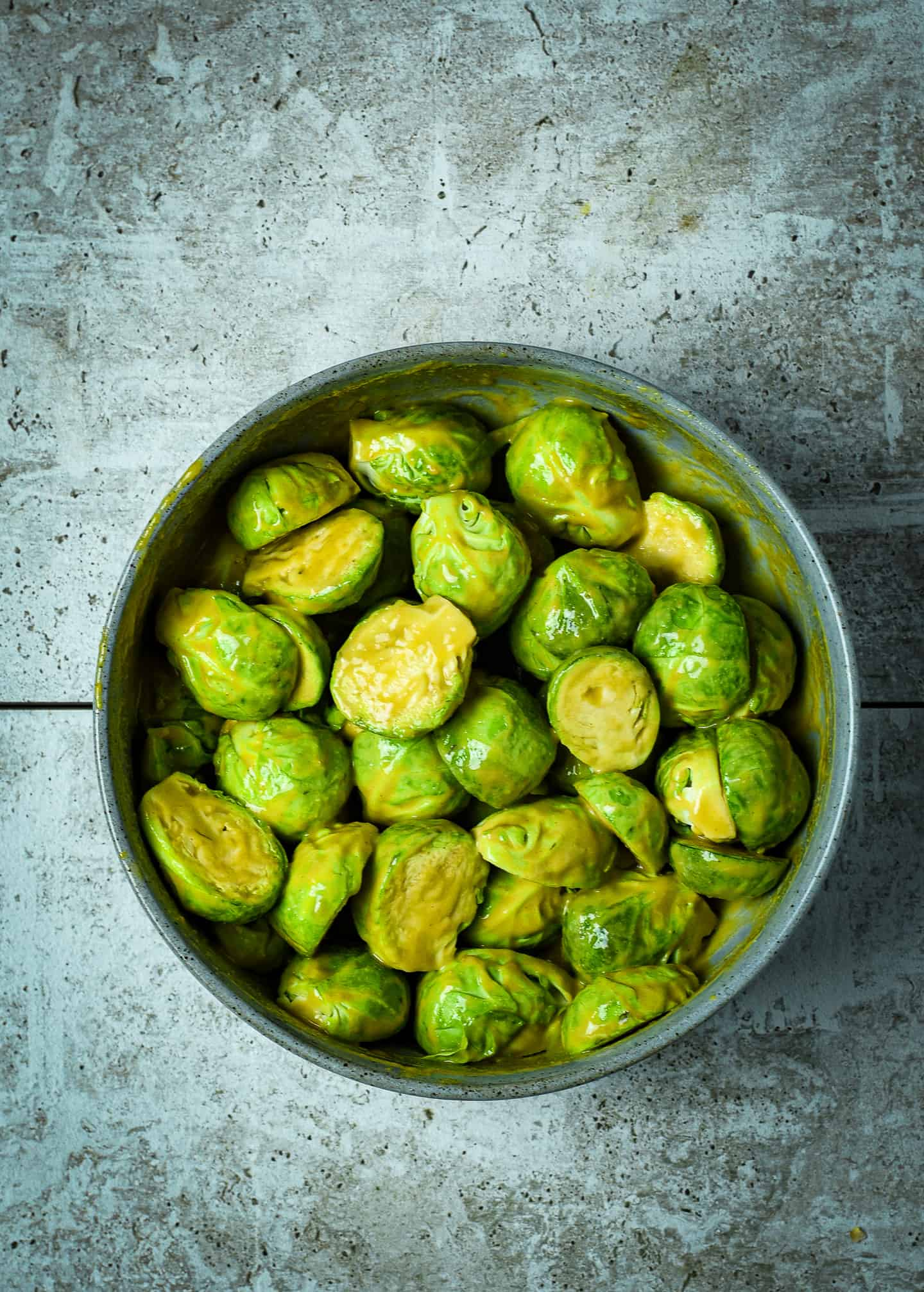 Brussels sprouts in bowl of marinade.