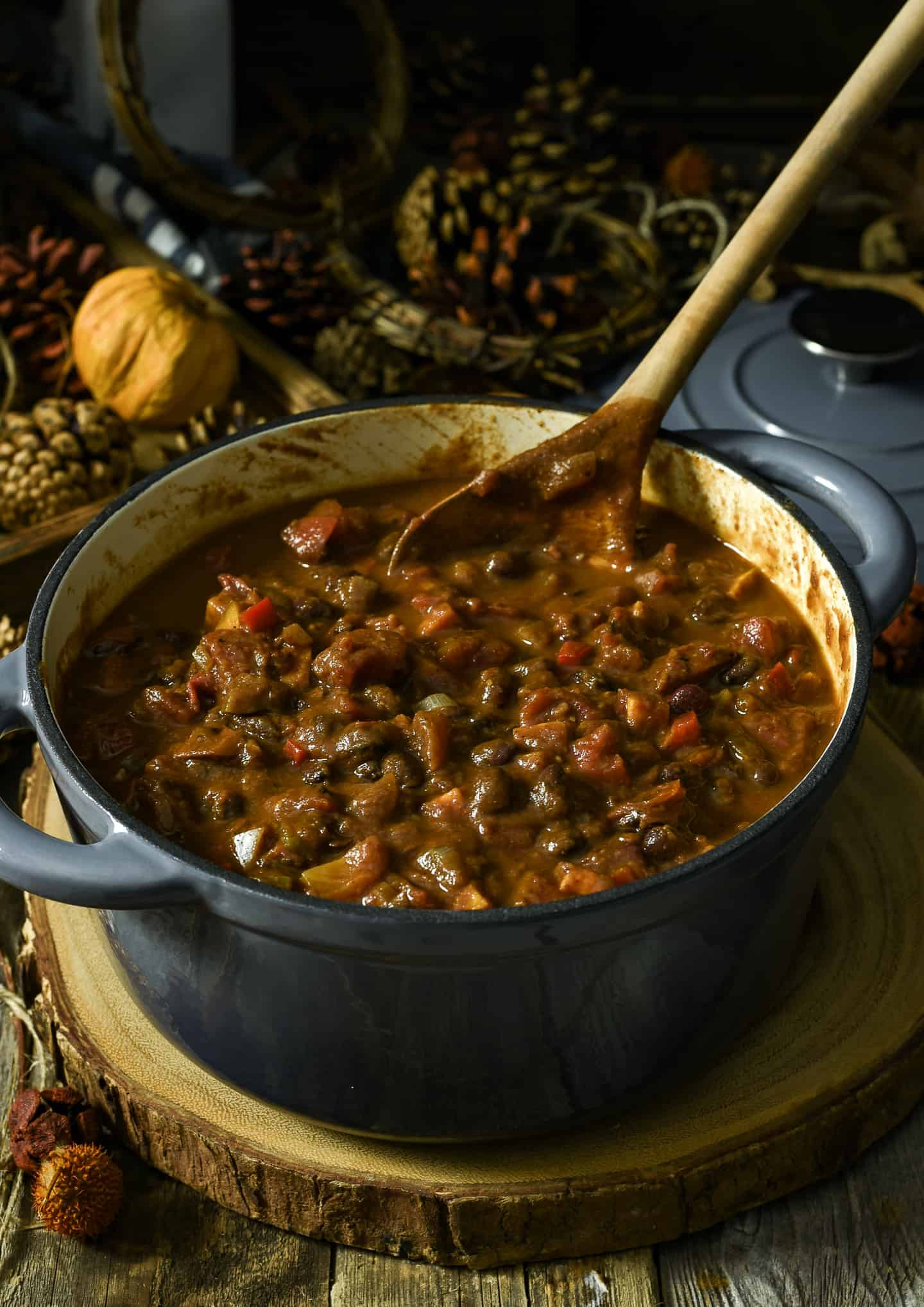 Pot of pumpkin chili with wooden serving spoon.