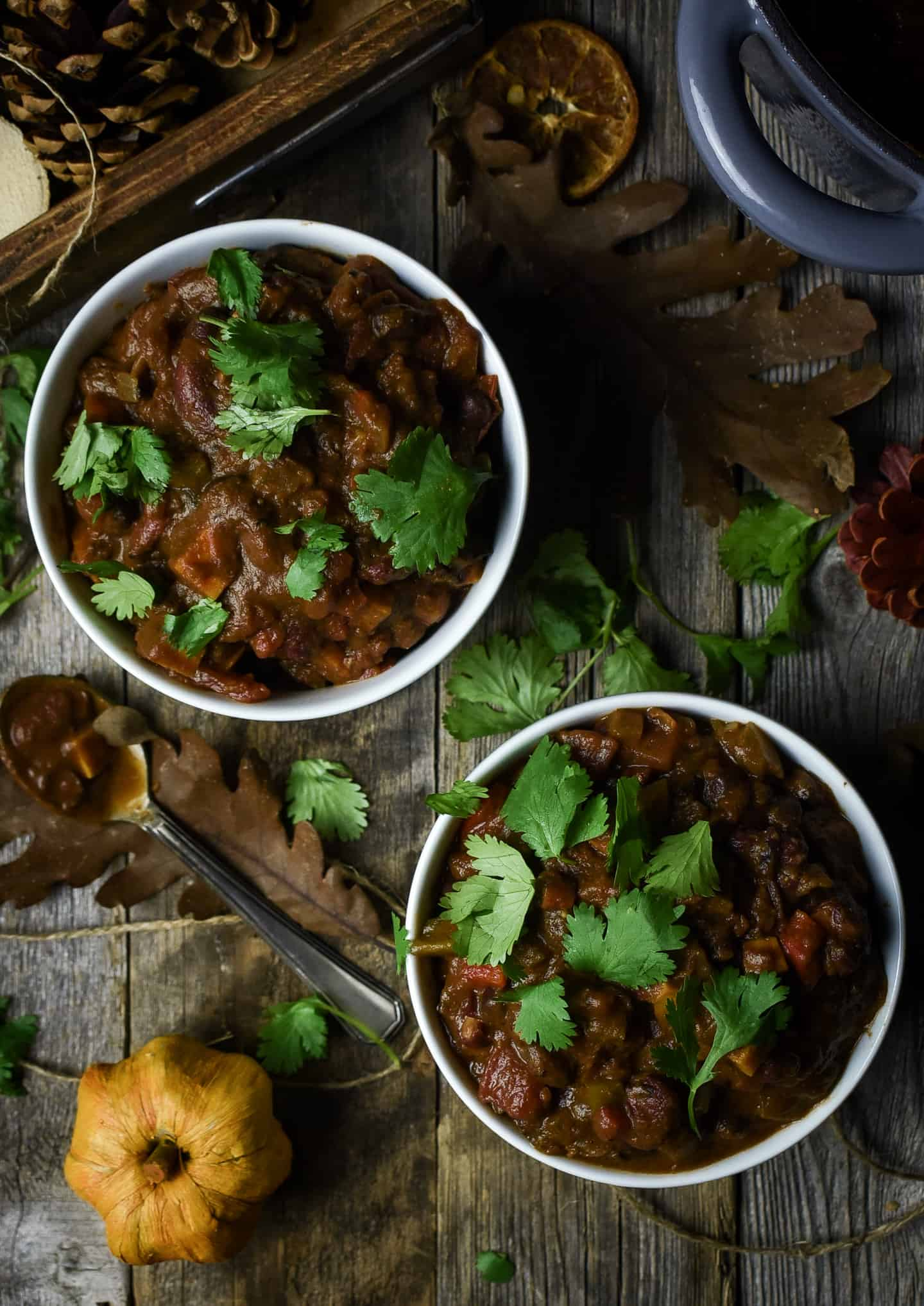 Two bowls of pumpkin chili topped with cilantro.