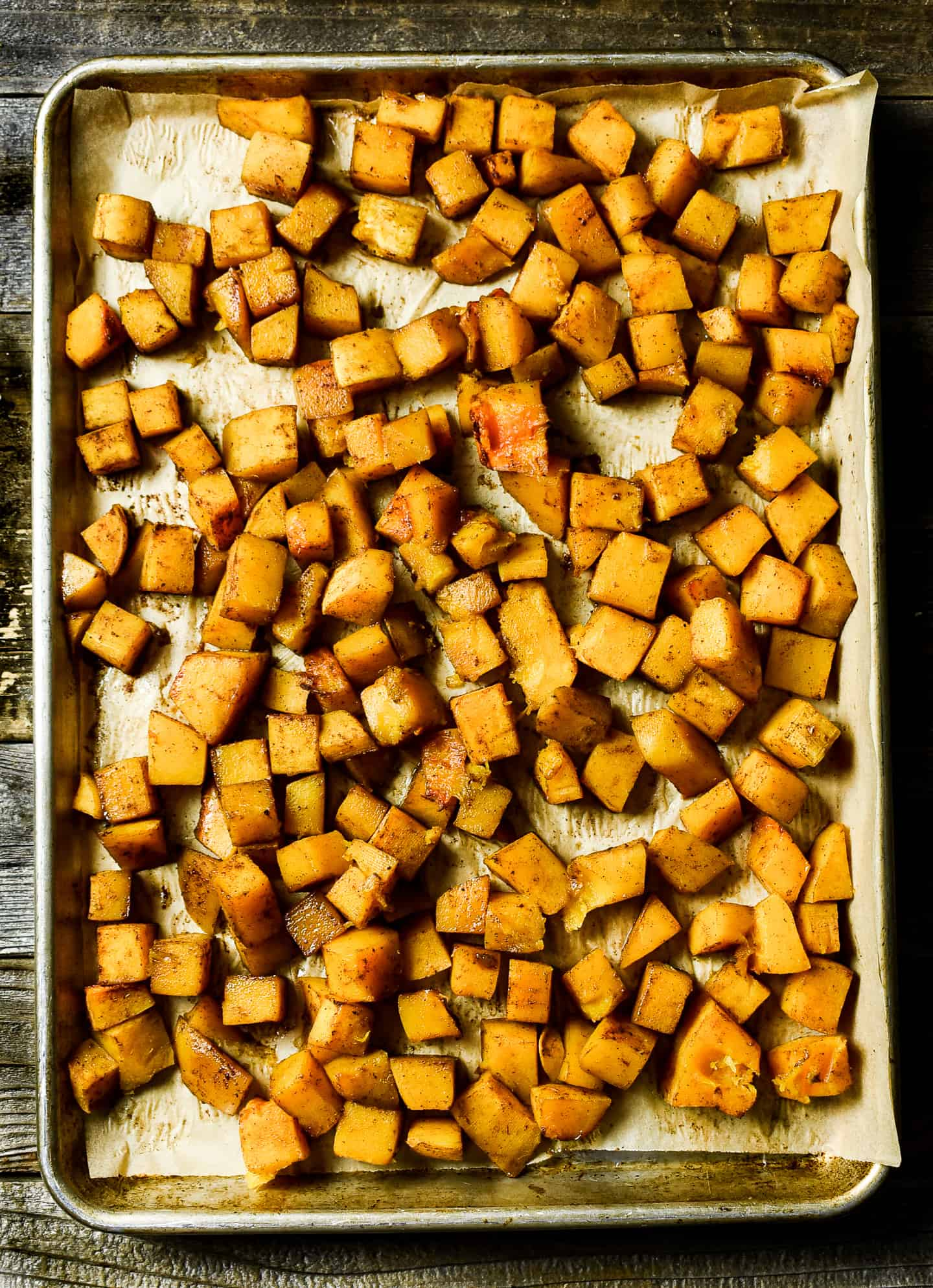 Roasted butternut squash on baking sheet with parchment paper.