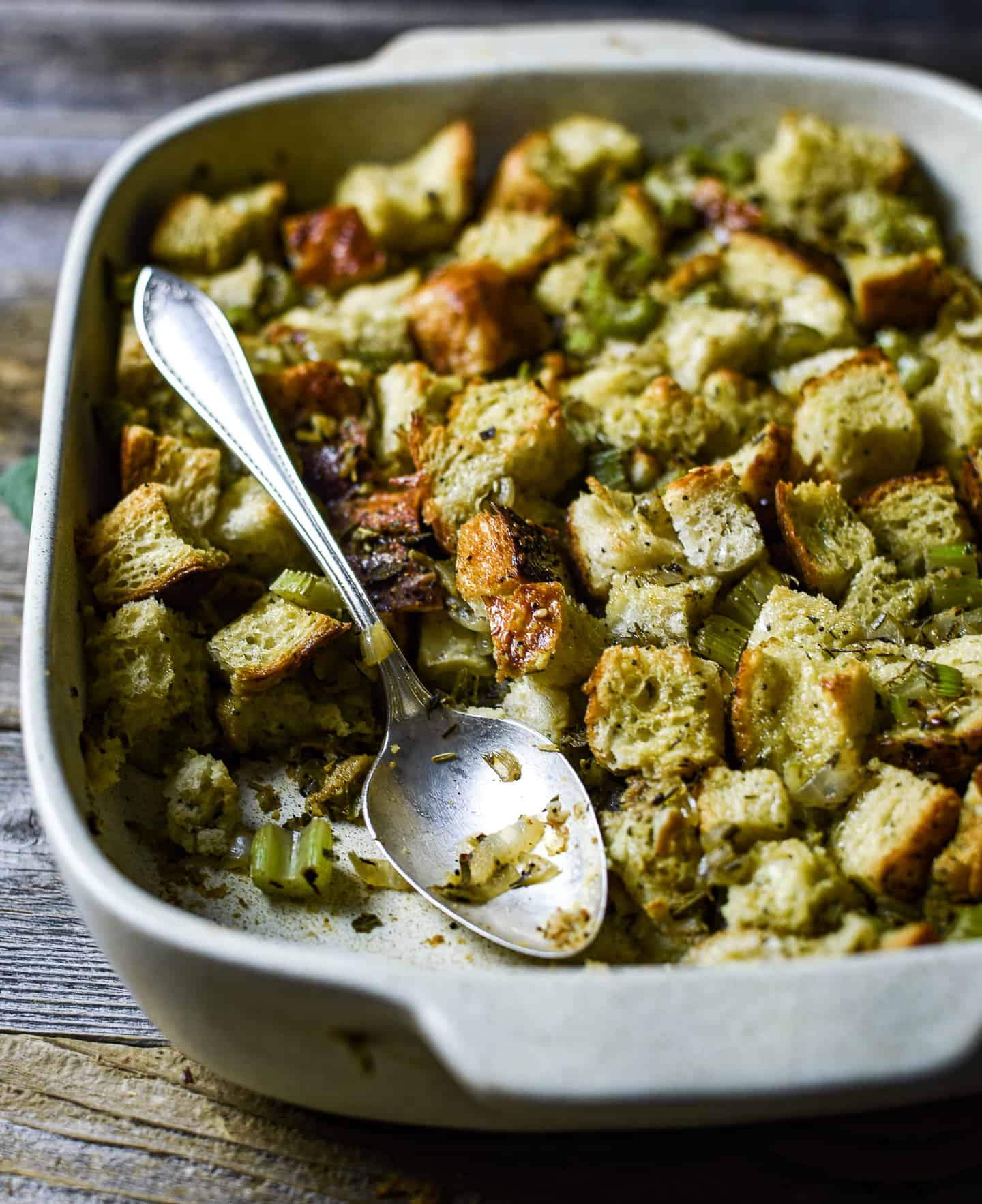 Spoon and vegan stuffing in baking dish.