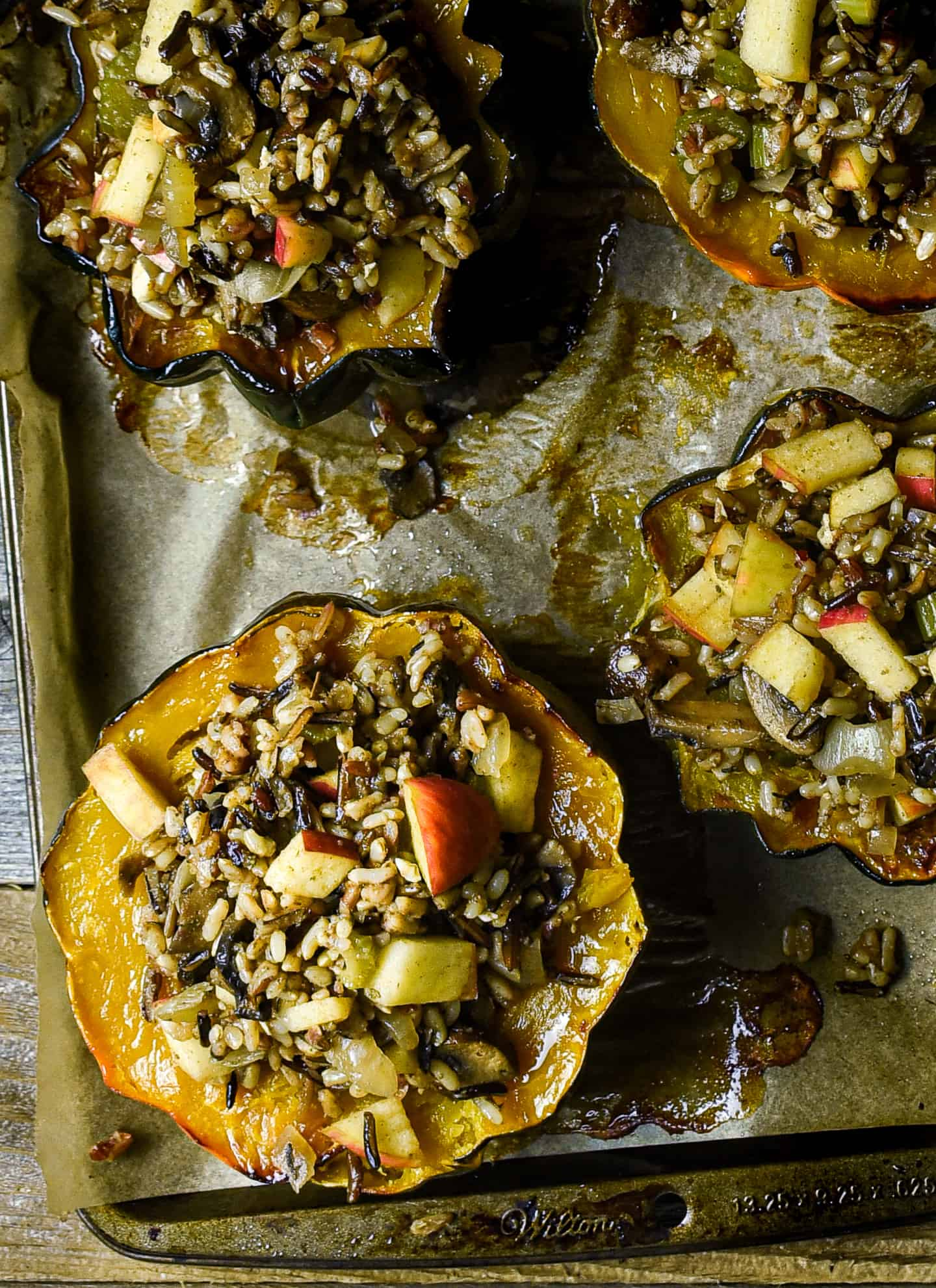 Roasted acorn squash on baking sheet with parchment paper.
