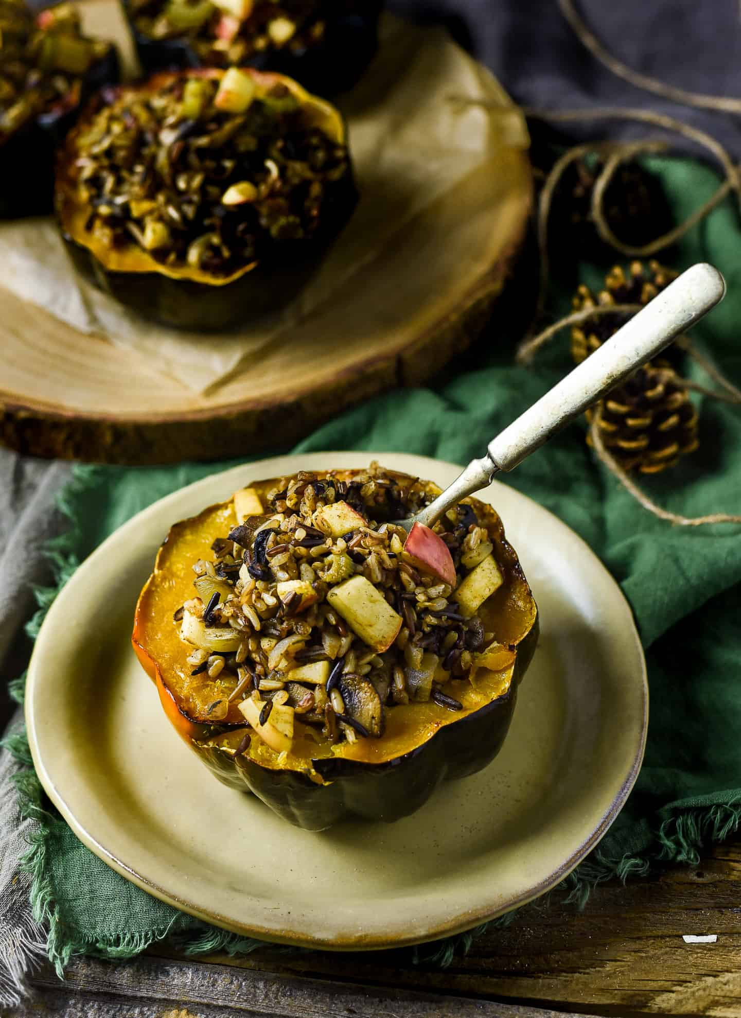 Stuffed acorn squash on plate with with fork in wild rice stuffing.