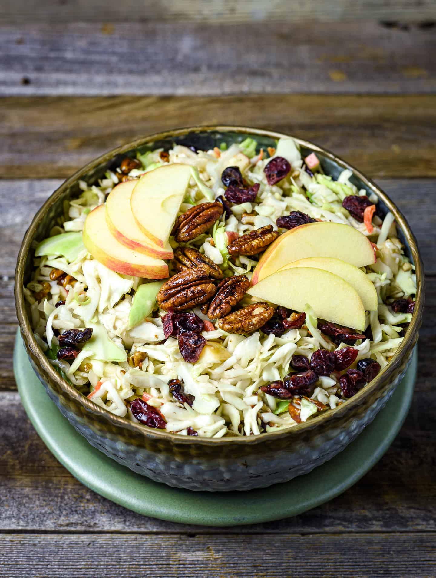 Apple cranberry coleslaw in bowl topped with pecans and apples.