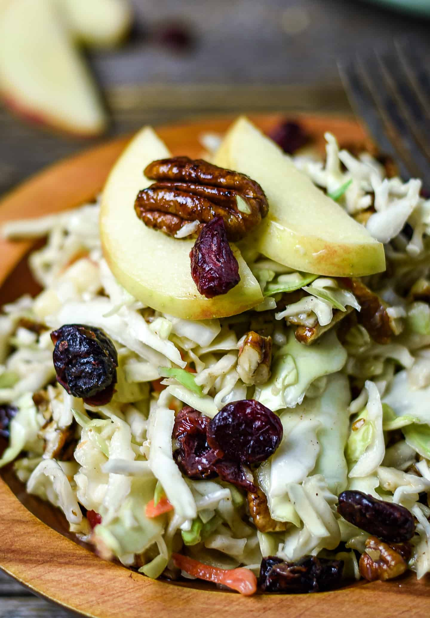 Pecans, apples, and cranberries on top of coleslaw.