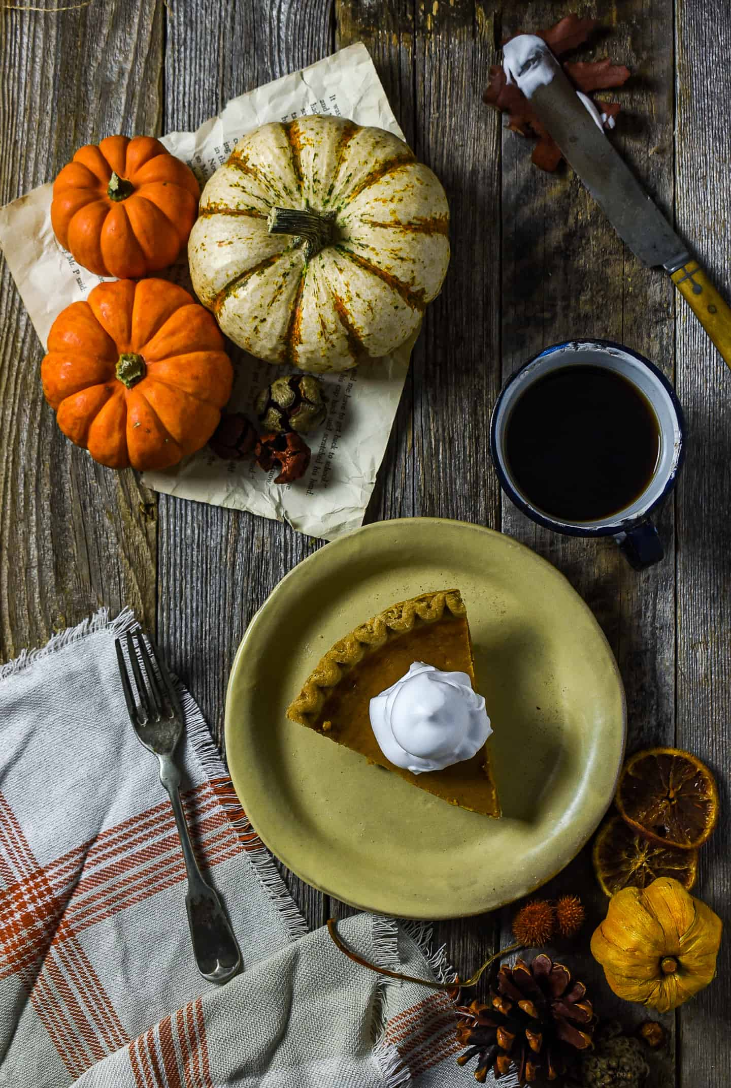 Pumpkin pie on plate with whipped cream on top.