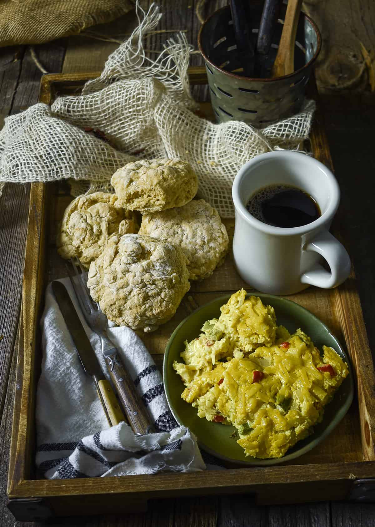 Vegan hash brown casserole on plate with biscuits and coffee.