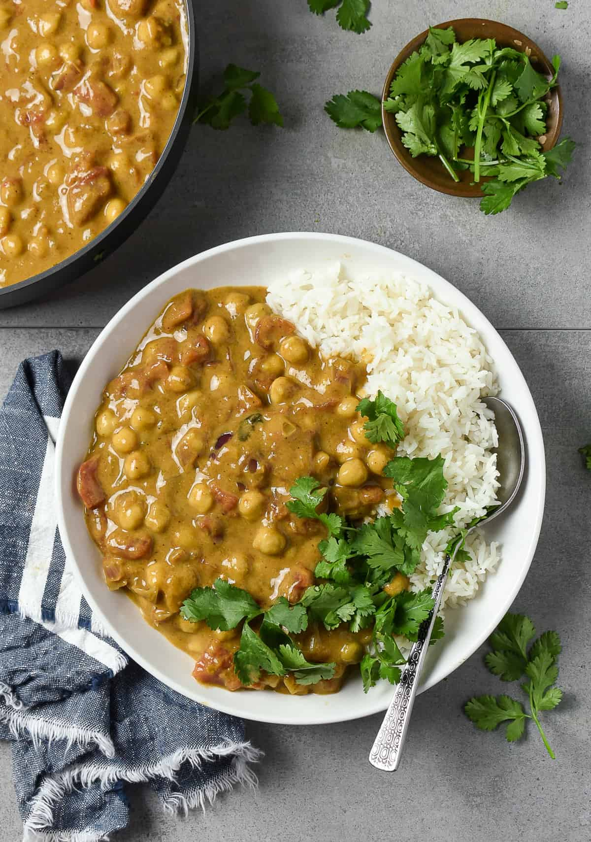 Chickpea curry and rice on white plate with a spoon.