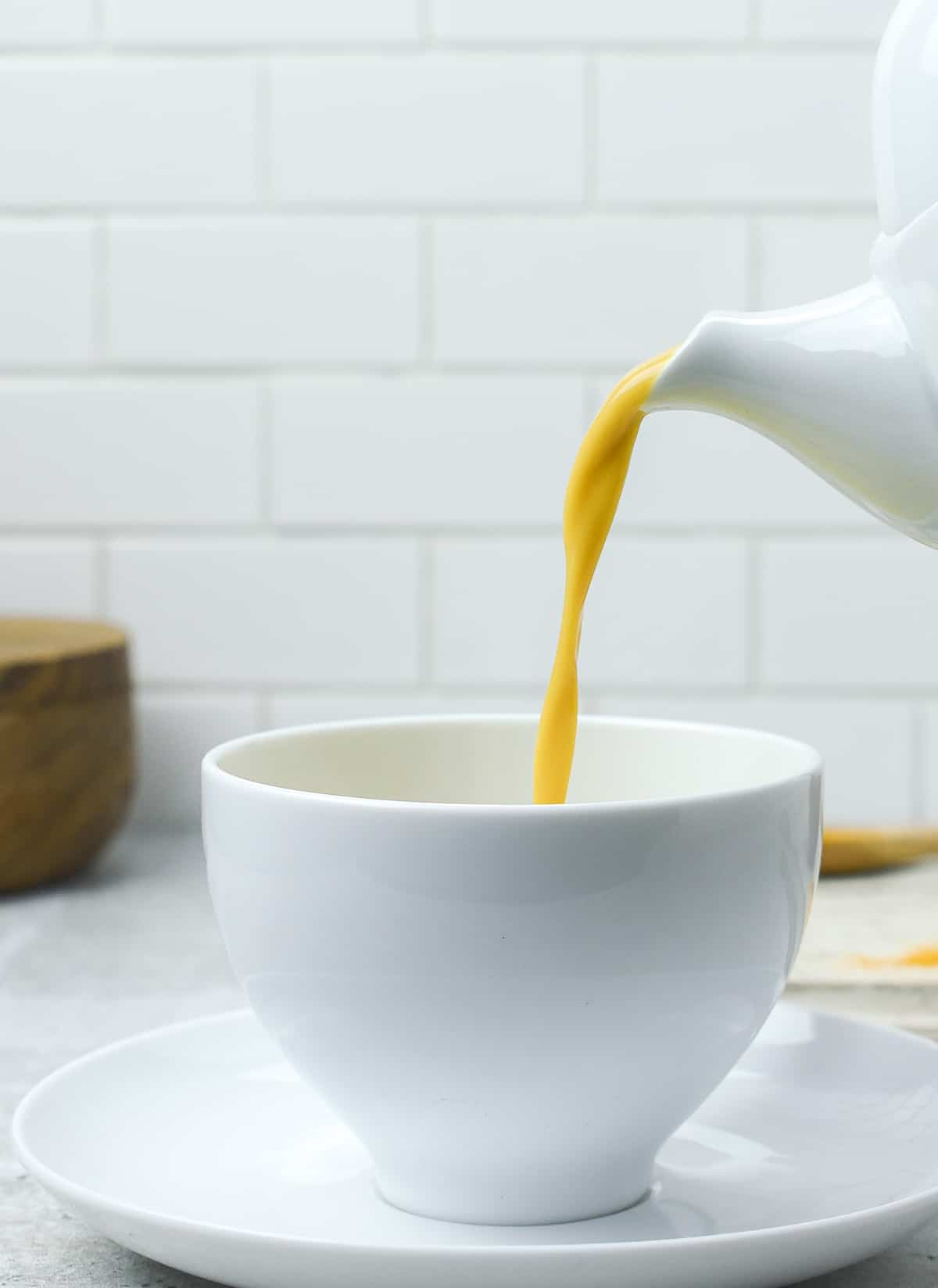 Golden milk latte being poured into cup.