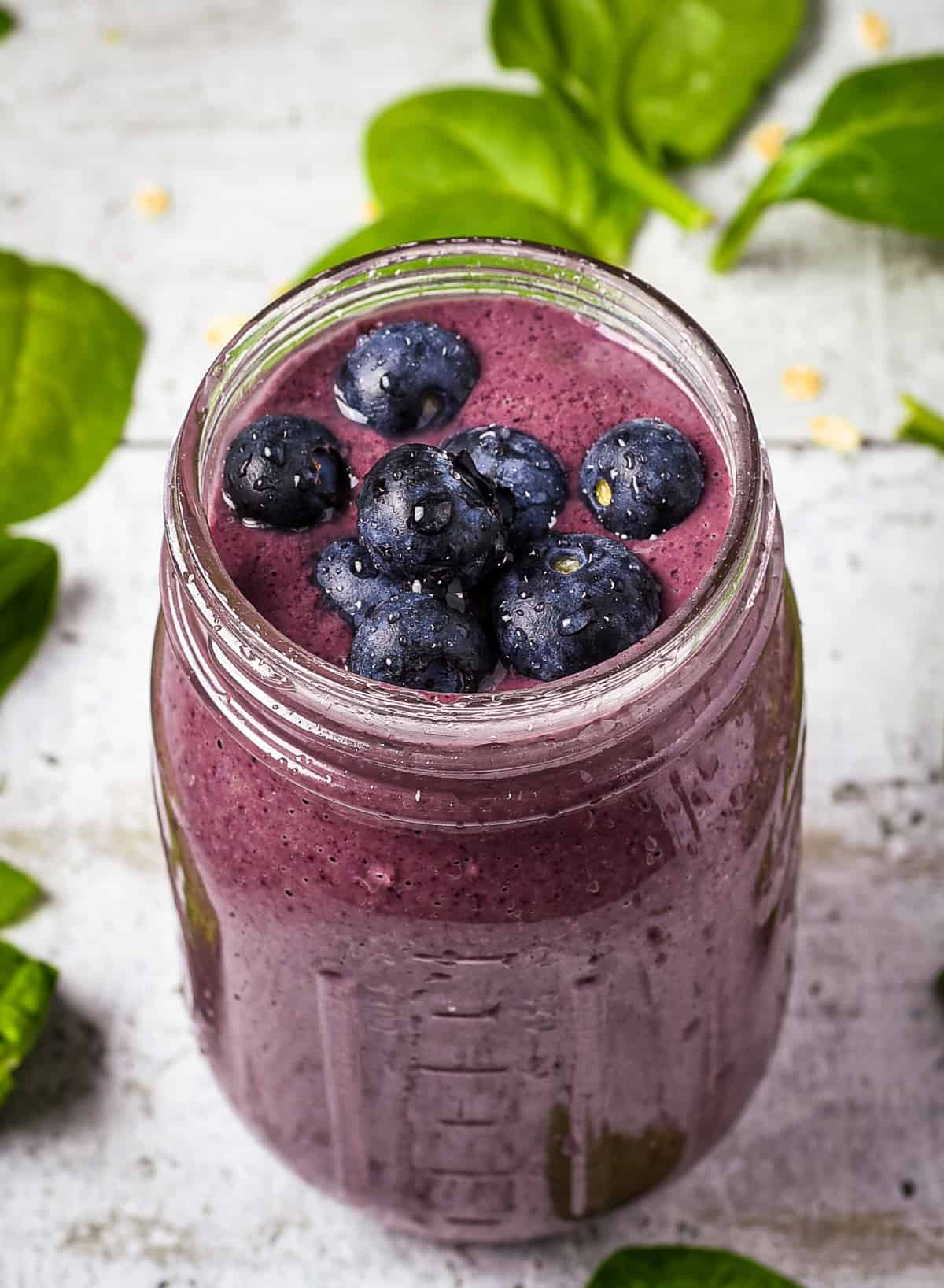 Spinach berry smoothie with fresh blueberries on top.