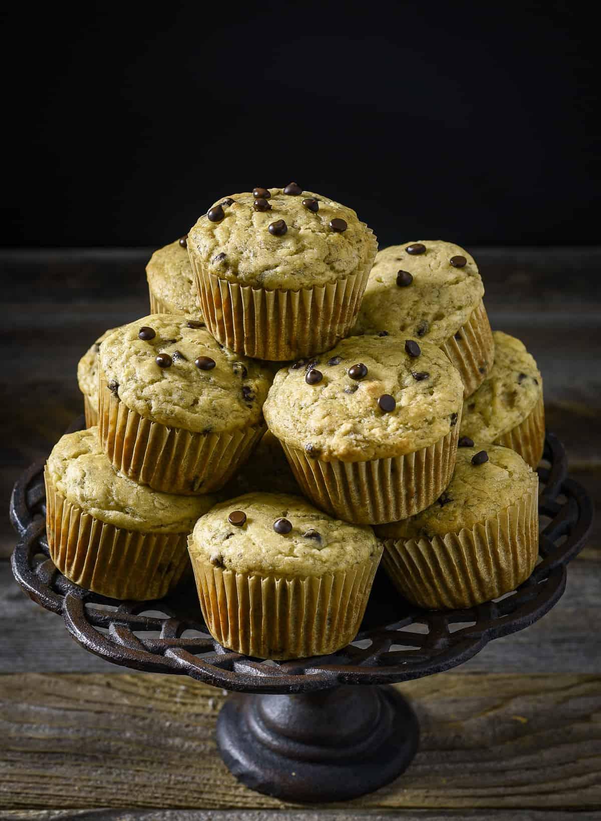 Vegan banana chocolate chip muffins stacked on cake stand.