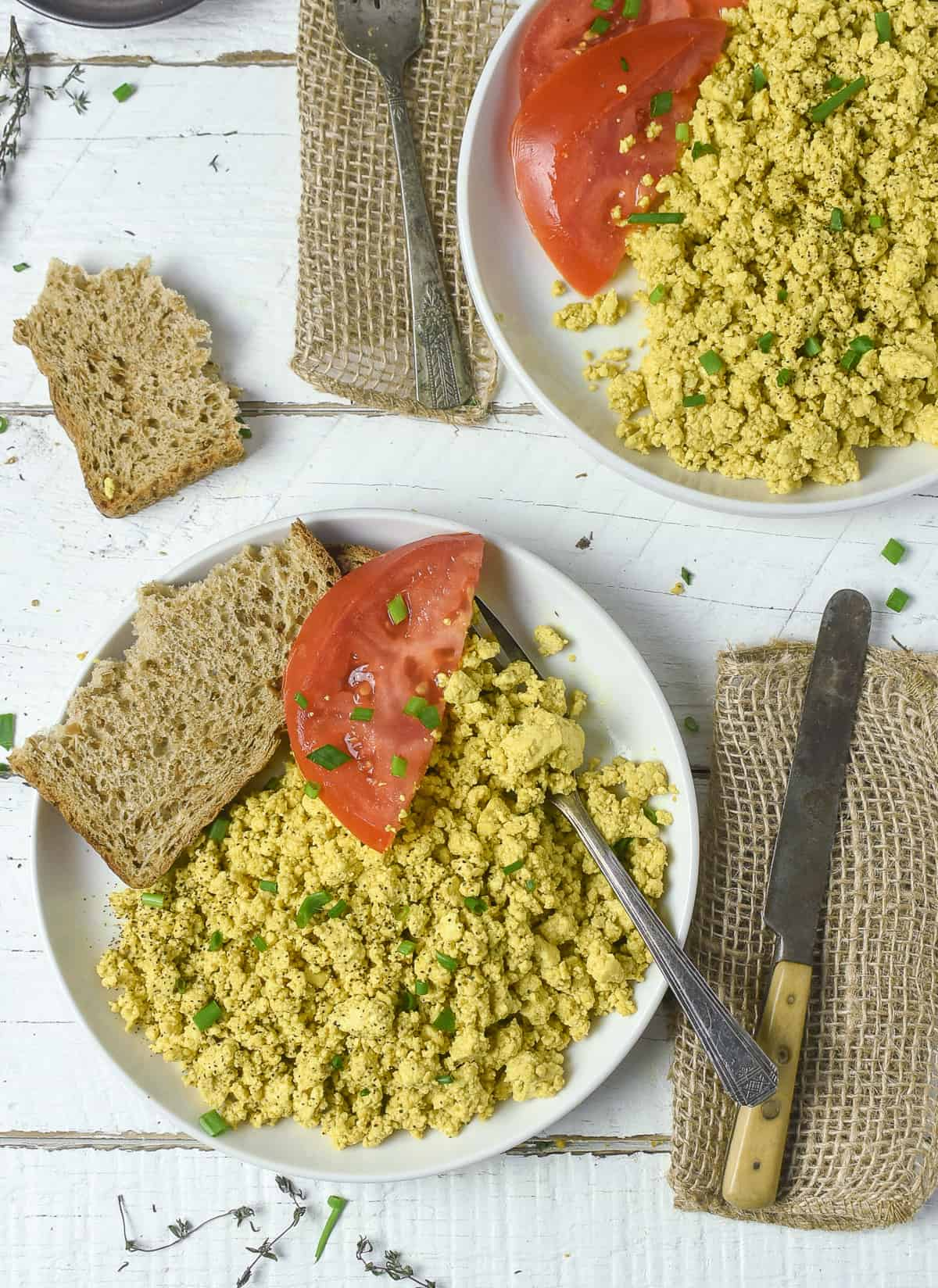 Tofu scramble on plate with toast and tomato.