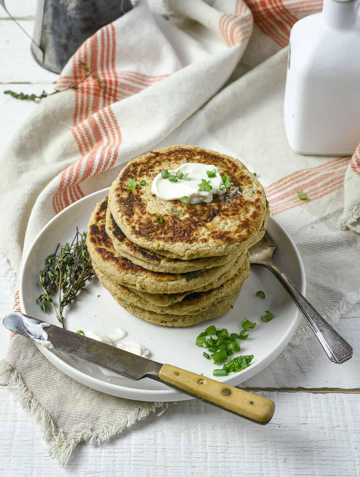 Potato pancakes on plate topped with vegan sour cream