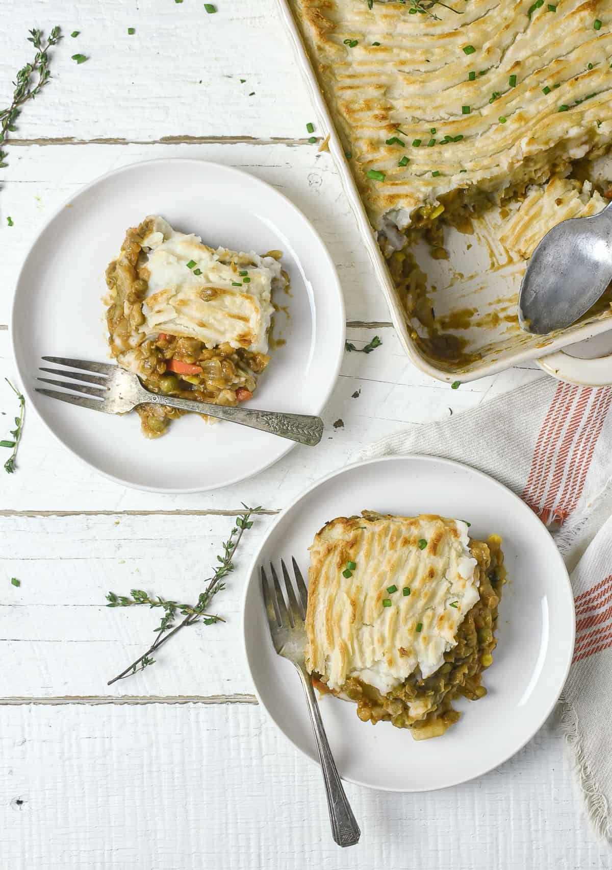 Two plates with vegan lentil shepherd's pie.